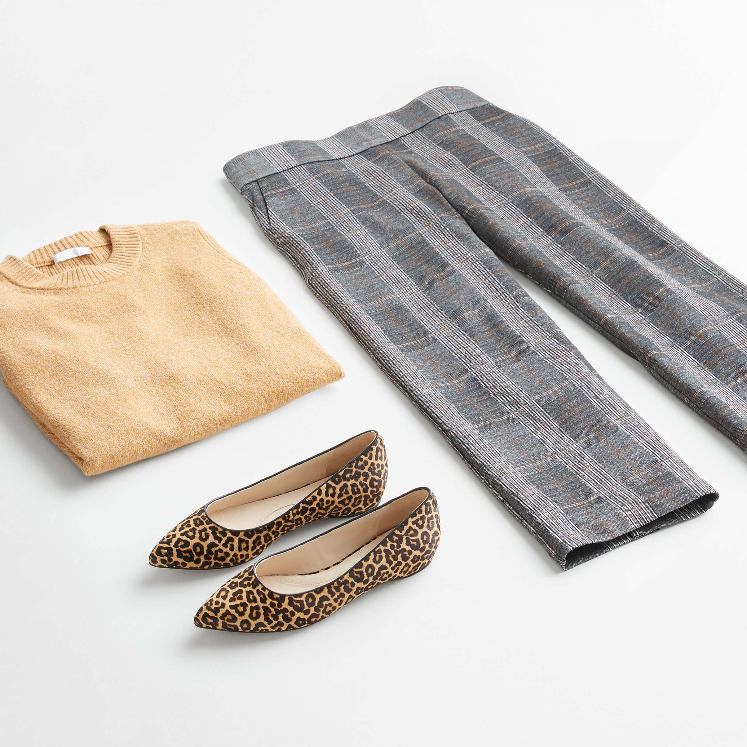 Stitch Fix Women's outfit laydown featuring grey wide-leg pants, camel crew neck pullover and brown animal-print flats.