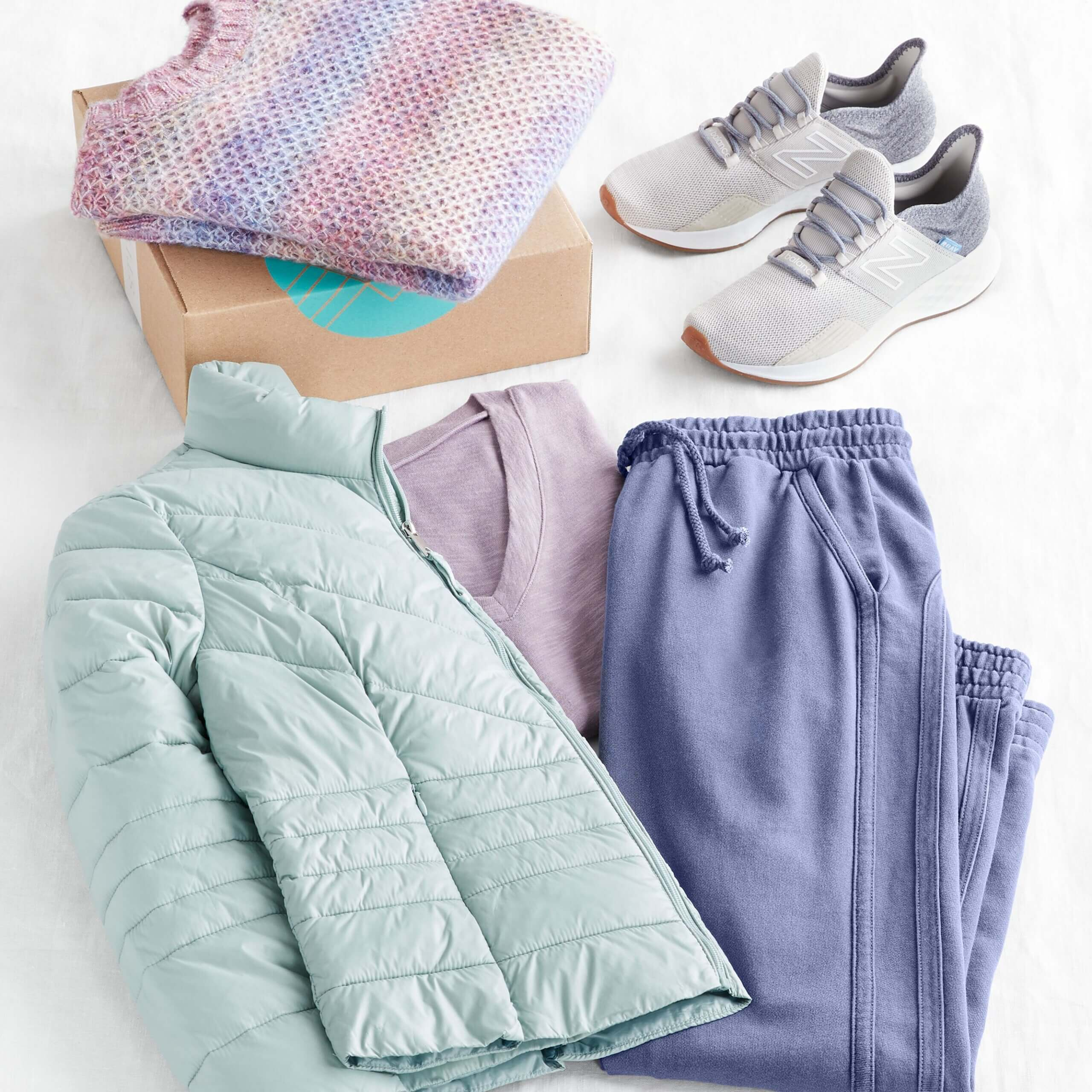 Stitch Fix Women's outfit laydown featuring mint puffer jacket, purple tee, blue jogger pants and grey sneakers, next to purple pullover on a Stitch Fix delivery box.