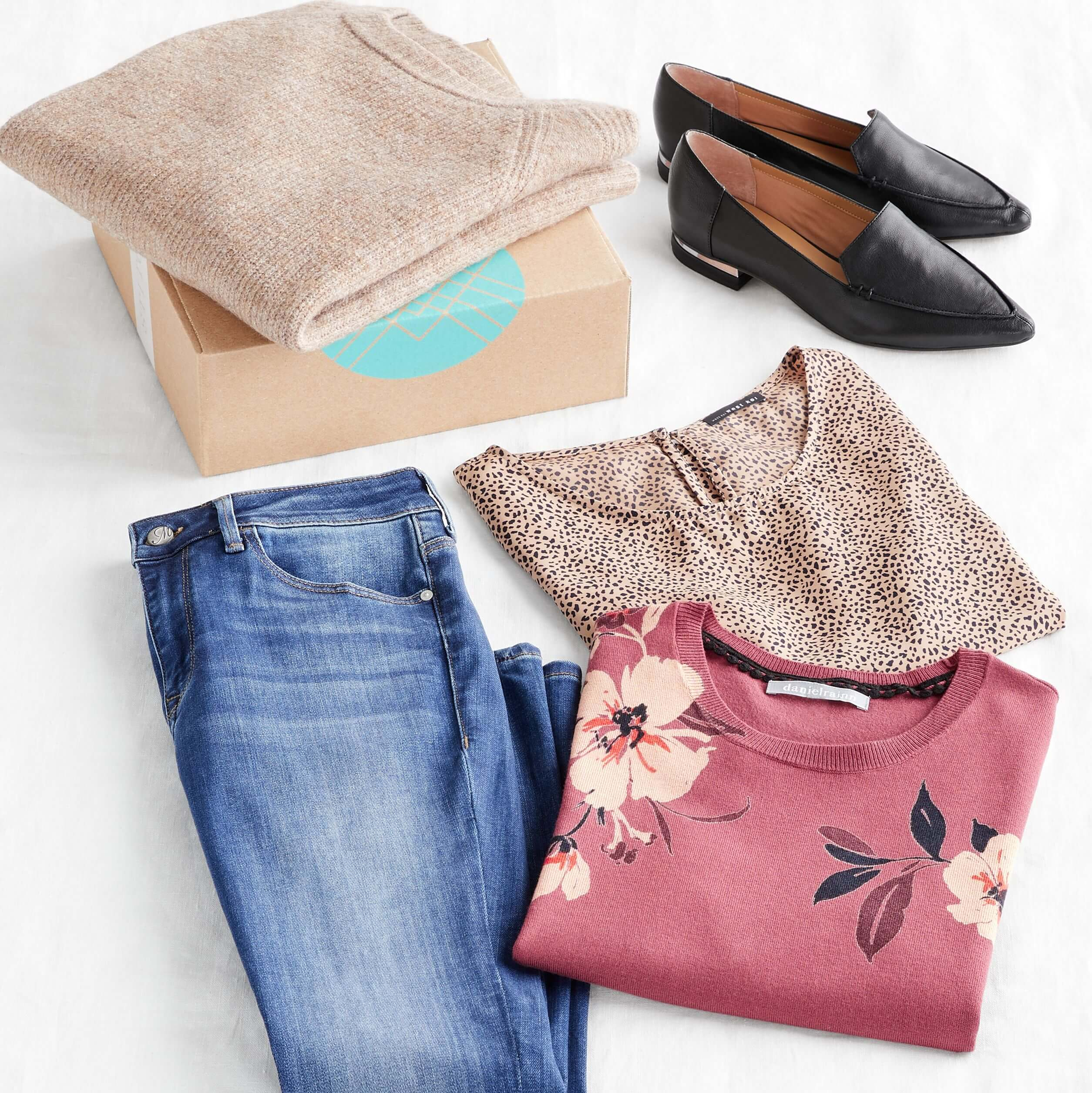 Stitch Fix Women's outfit laydown featuring a tan pullover on a Stitch Fix delivery box next to black loafers, blue jeans, brown animal-print shirt and pink floral pullover.