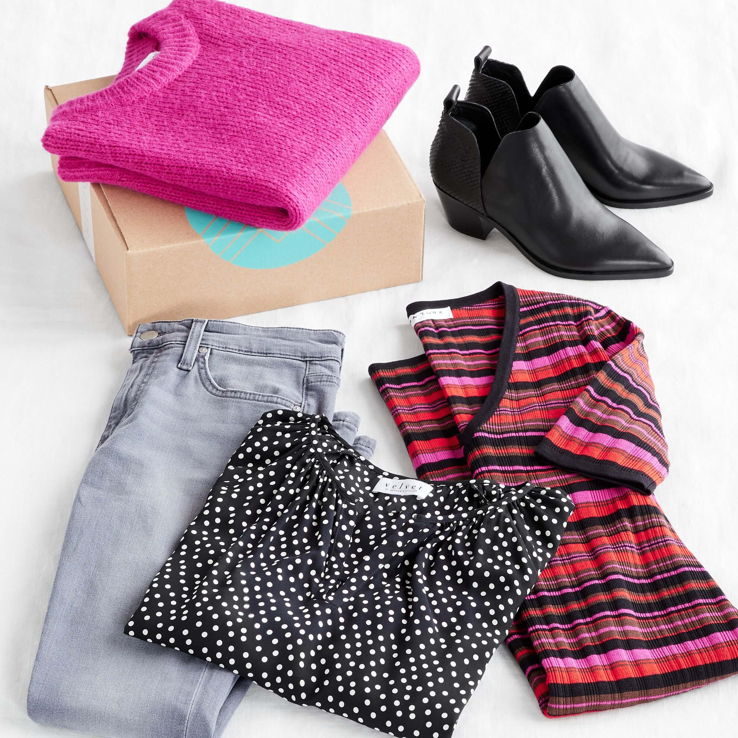 Stitch Fix Women's outfit laydown featuring a bright pink crew neck sweater on a Stitch Fix delivery box, next to black booties, pink striped sweater dress, black polka dot top and grey jeans.