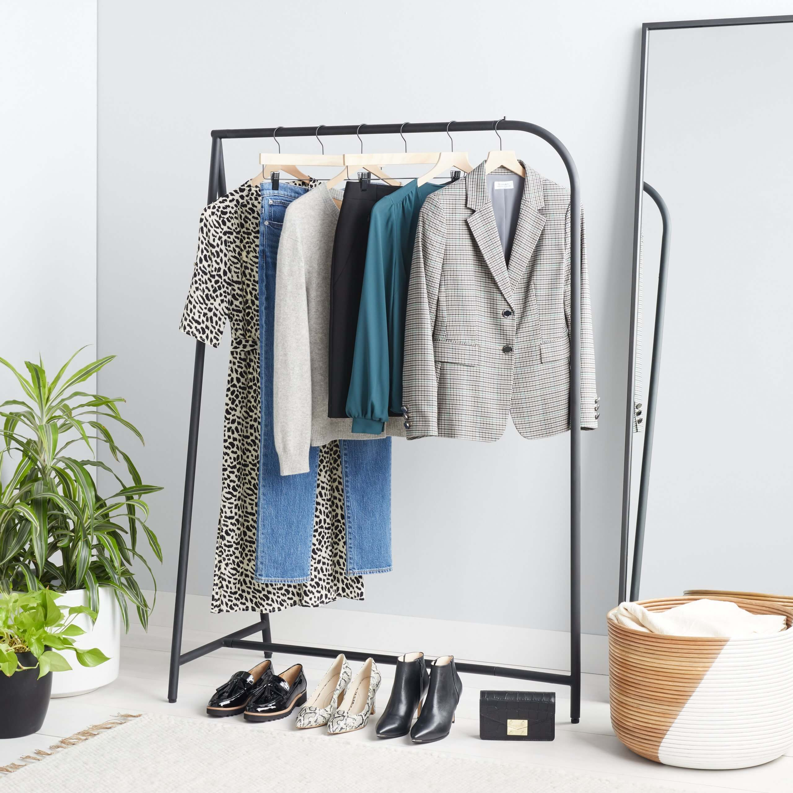 Stitch Fix Women's rack image featuring grey blazer, teal blouse, black skirt, grey sweater, blue jeans and black animal print tie-waist dress hanging on black rack next to black purse, black booties, white animal print pumps and black loafers on the floor.