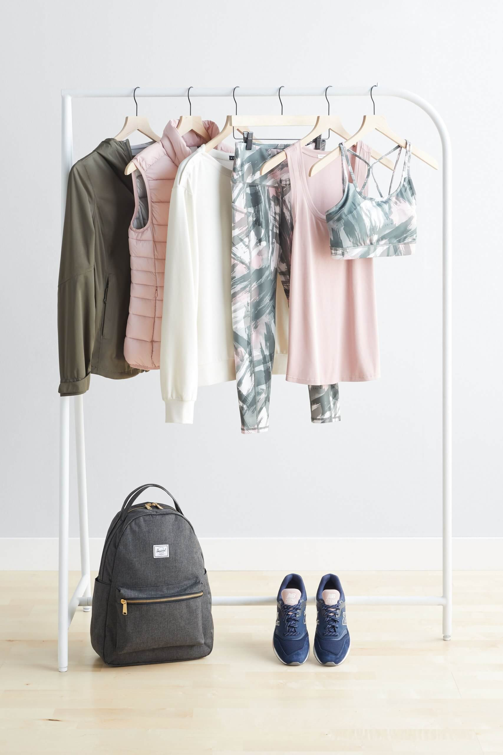 Stitch Fix Women's olive jacket, pink puffer vest, white crew neck sweatshirt, tropical print leggings, pink tank and tropical print sports bra on a rack. Grey backpack and navy sneakers on the floor.