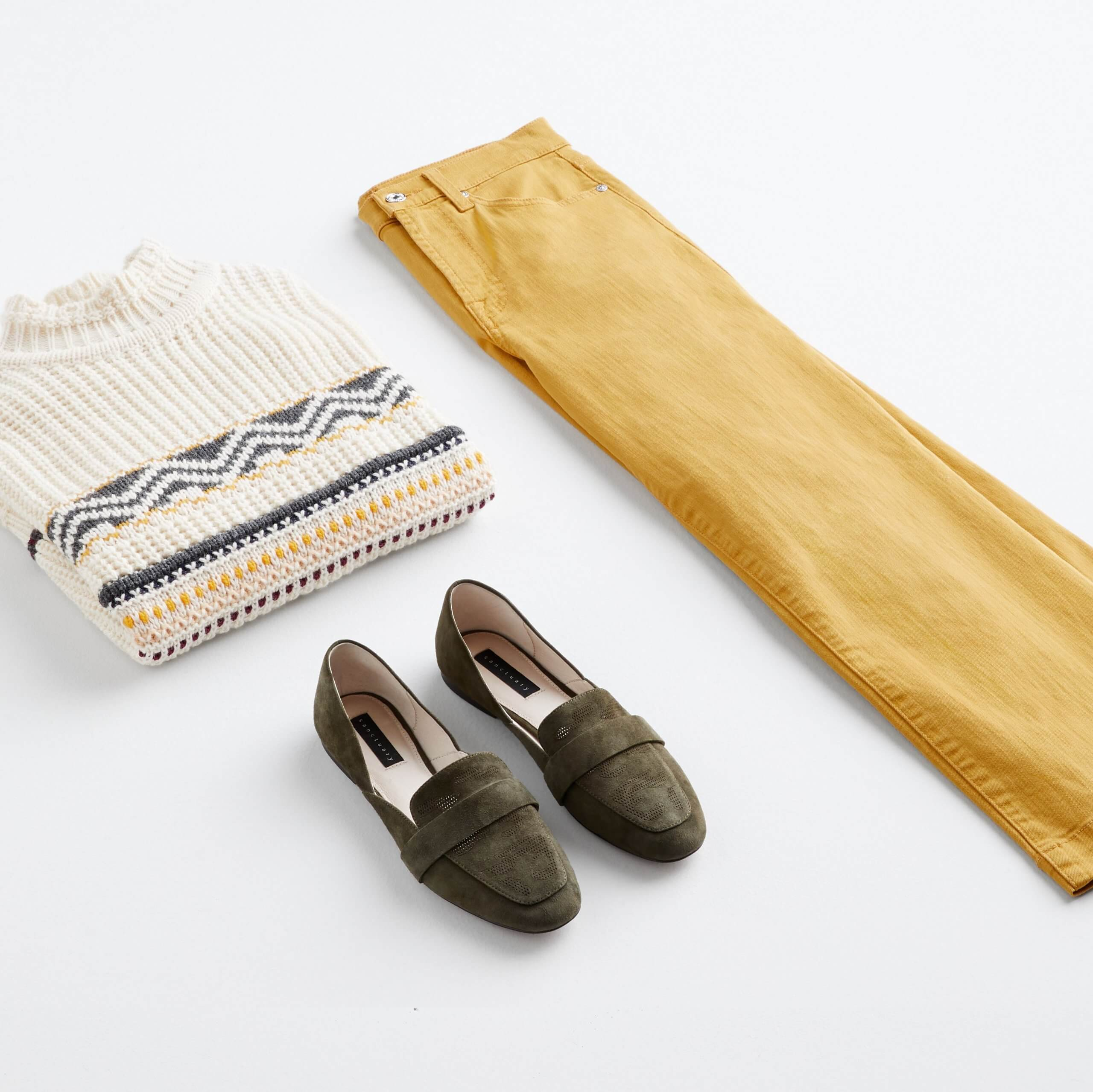 Stitch Fix Women's outfit laydown featuring mustard wide-leg jeans, cream mock neck sweater and dark green loafers.