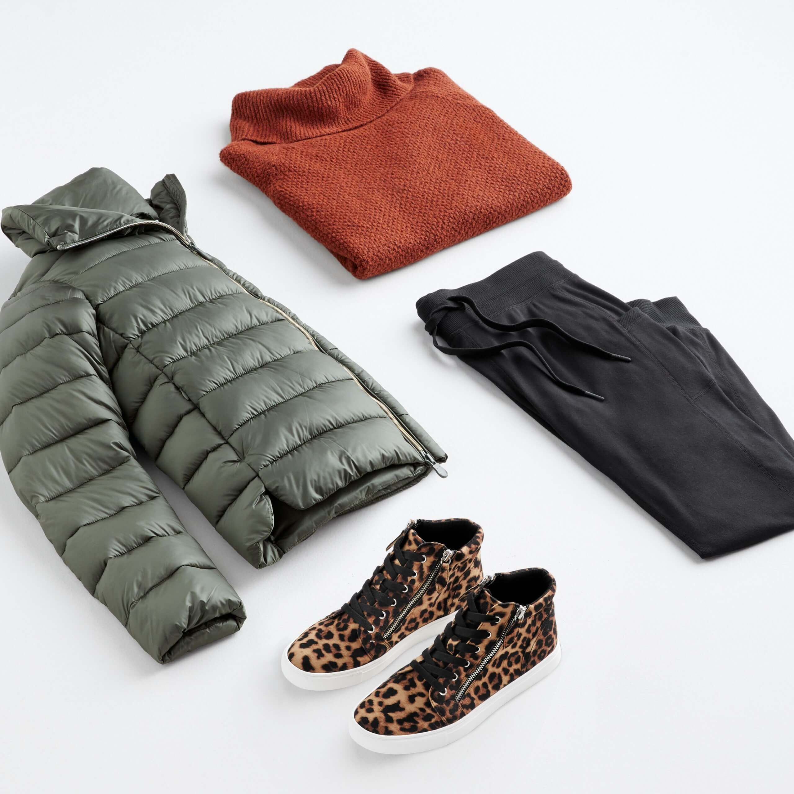 Stitch Fix Women's outfit laydown featuring green puffer jacket, burnt orange turtleneck pullover sweater, black jogger pants and cheetah-print high top sneakers.
