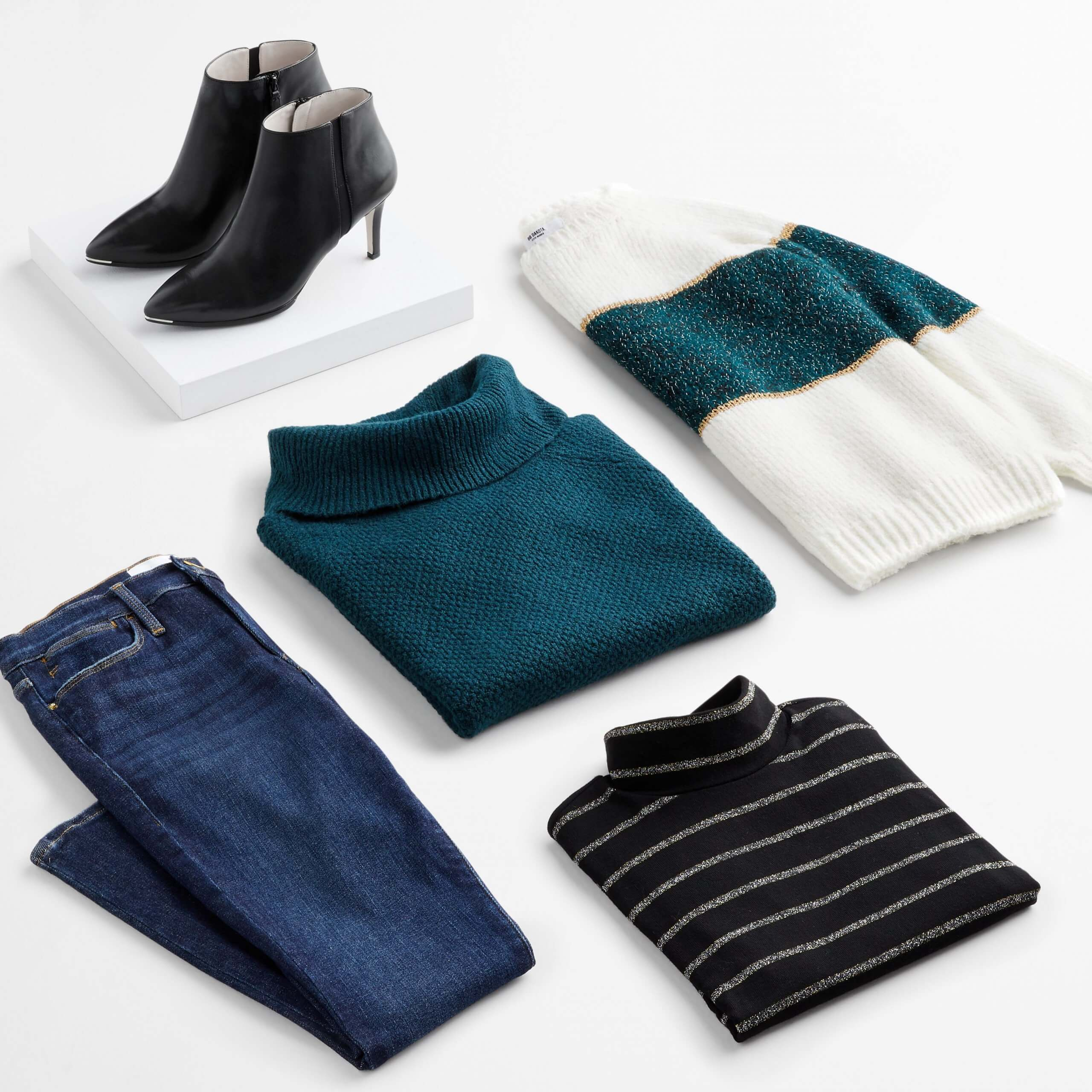 Stitch Fix Women's outfit laydown featuring skinny jeans, teal green turtleneck sweater, white and green pullover, black striped turtleneck, and black heeled booties on a white box.