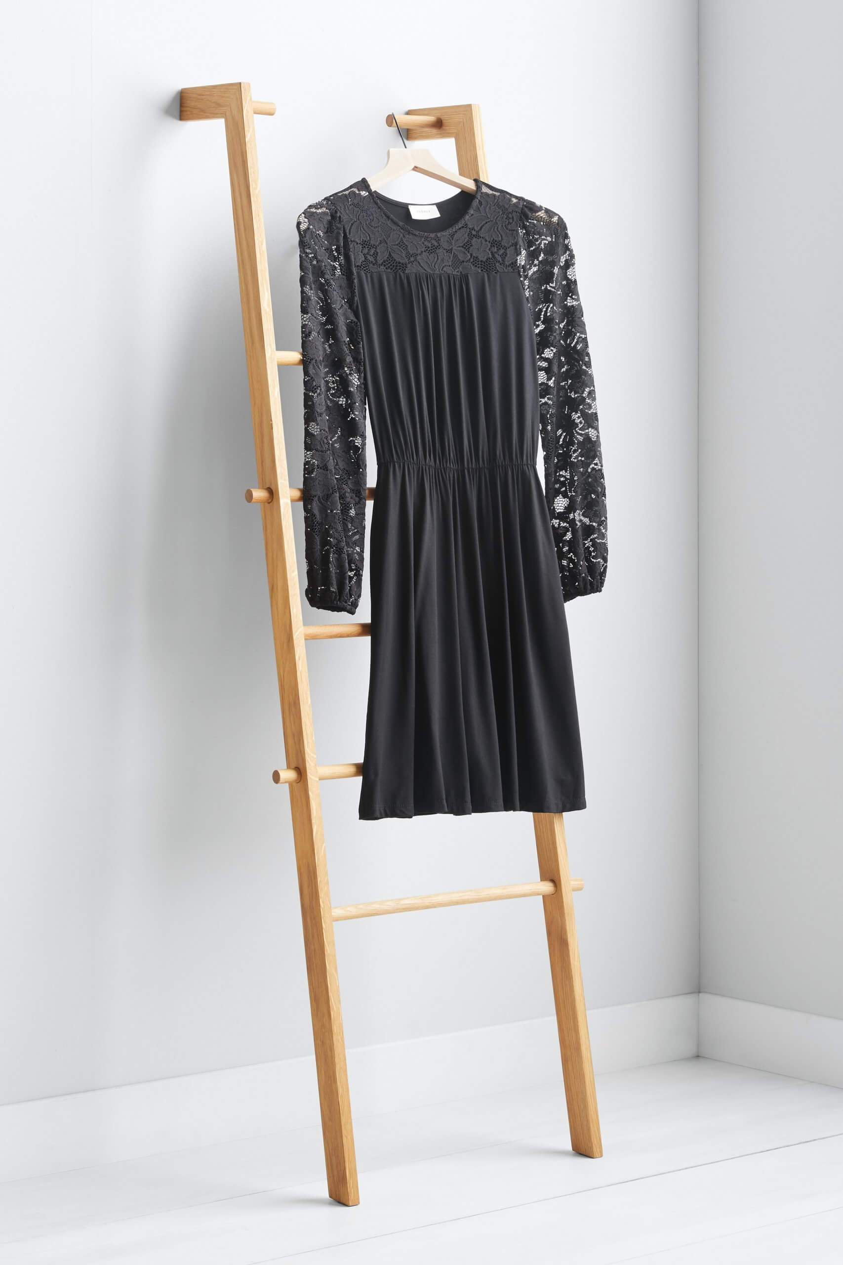 Stitch Fix Women's black dress with lace sleeves hanging on a wooden ladder.