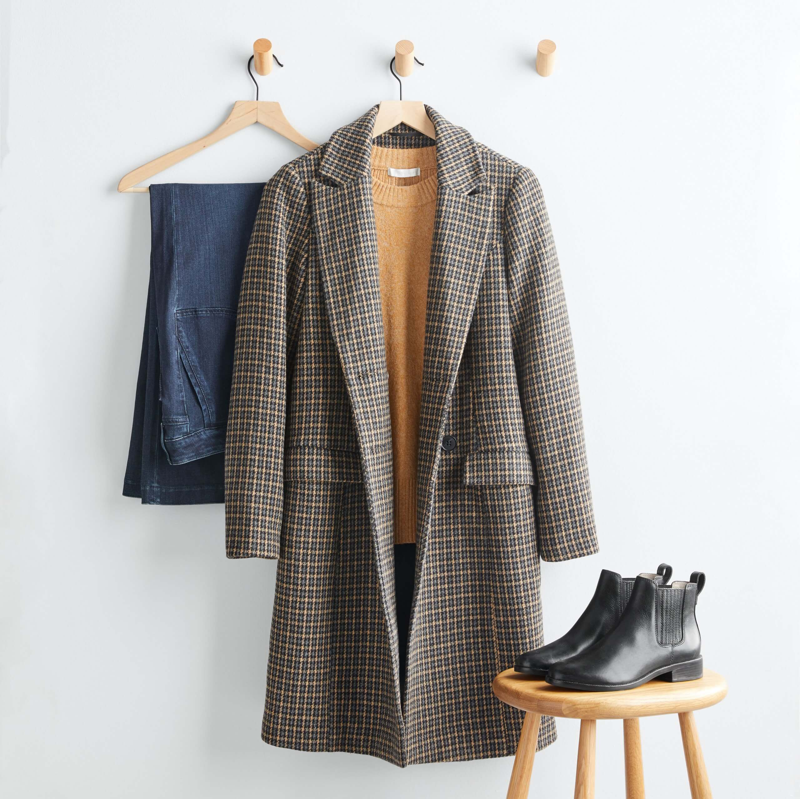Stitch Fix Women's outfit featuring brown plaid coat over mustard sweater hanging on wooden hanger, dark wash jeans on wooden hanger next to black leather booties on wooden stool.