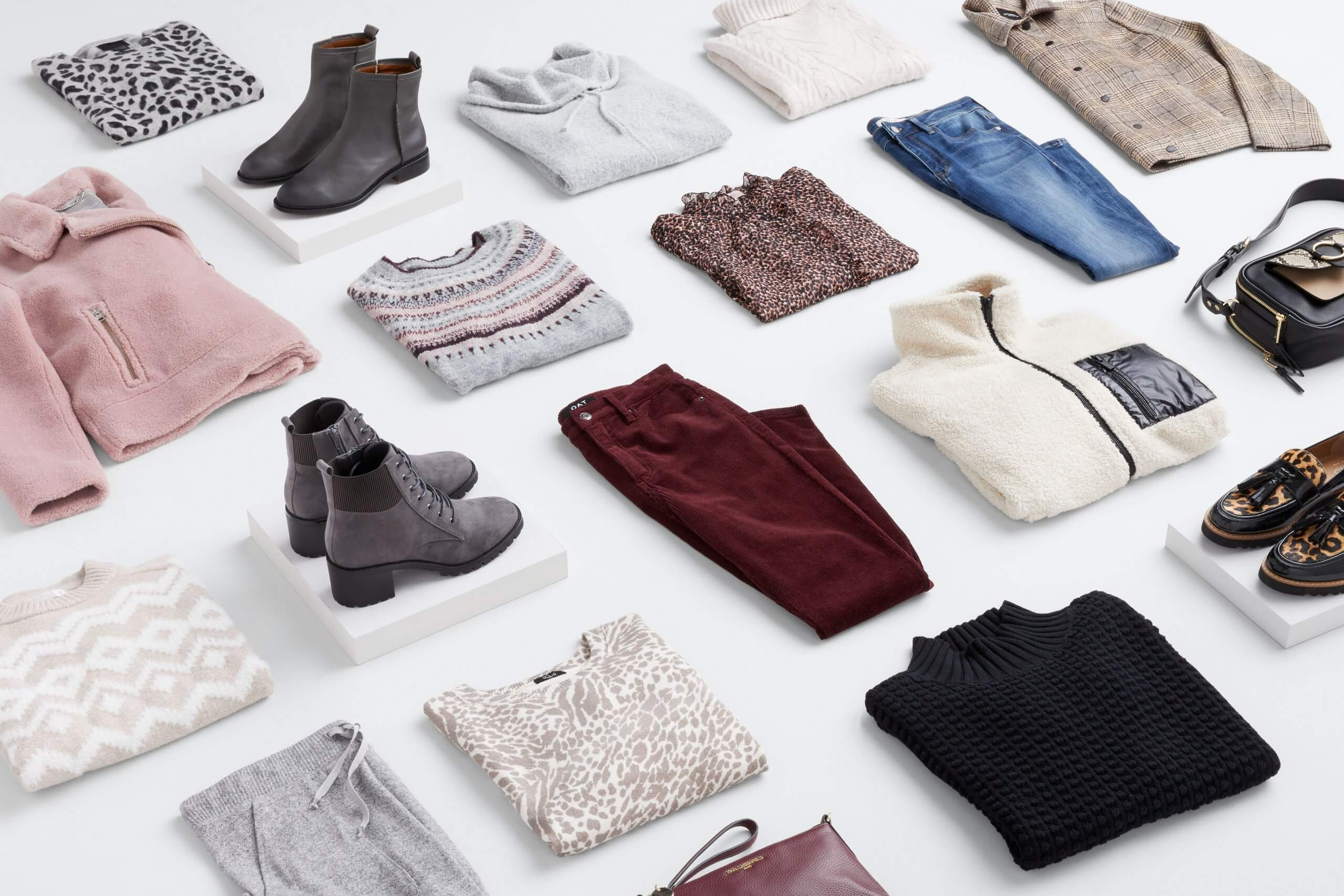 Stitch Fix Women's outfit laydown featuring pink sherpa jacket, grey and black animal print crew neck sweater, grey booties, grey cowl neck pullover, cream cable knit pullover sweater, tan plaid jacket, tan fairisle sweater, grey heeled booties, burgundy corduroy pants, brown animal print shirt, blue jeans, grey jogger pants, white and cream animal print sweatshirt, black turtleneck sweater and black animal print loafers.