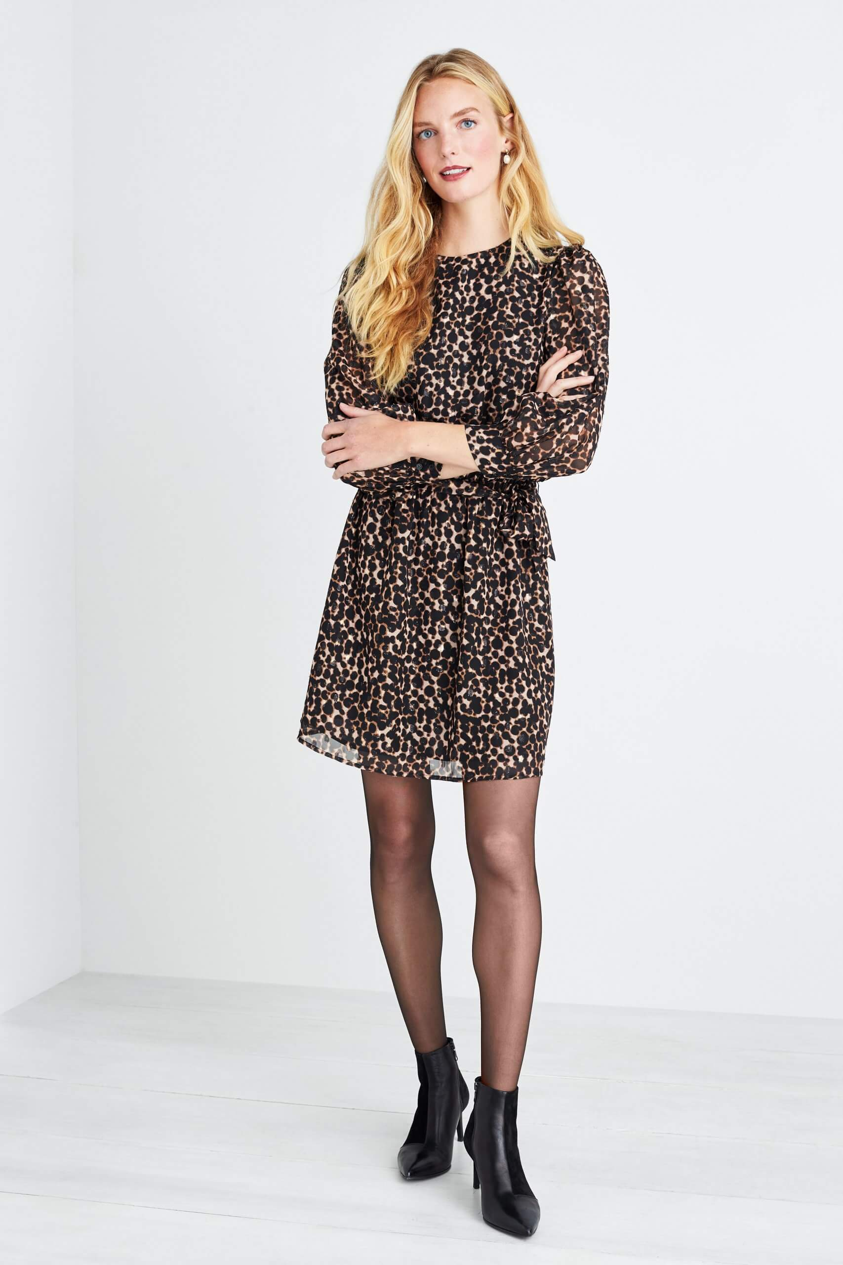 Stitch Fix Women's model wearing a black leopard print dress that hits just above the knees with black tights and black ankle booties.