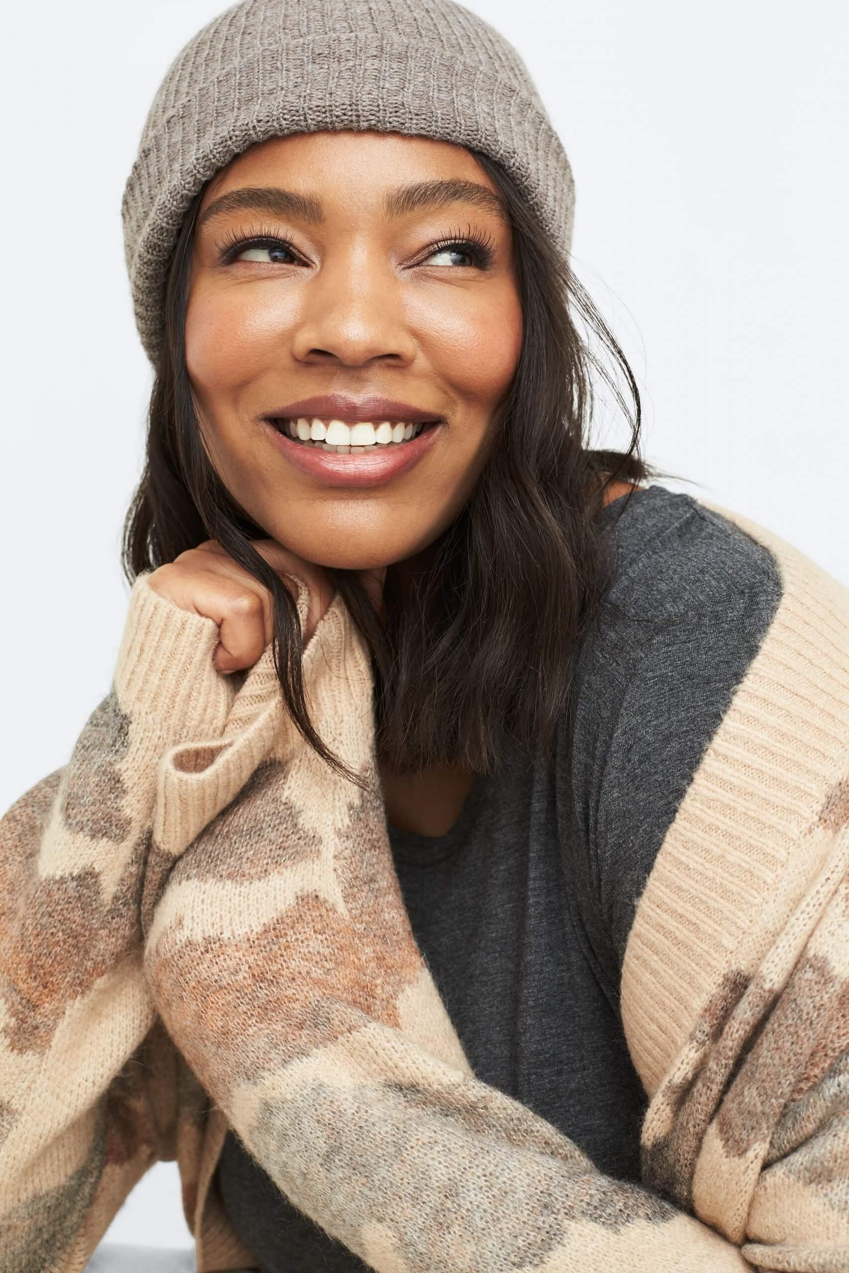 Stitch Fix Women's model wearing a grey beanie, grey knit top and tan printed cardigan.