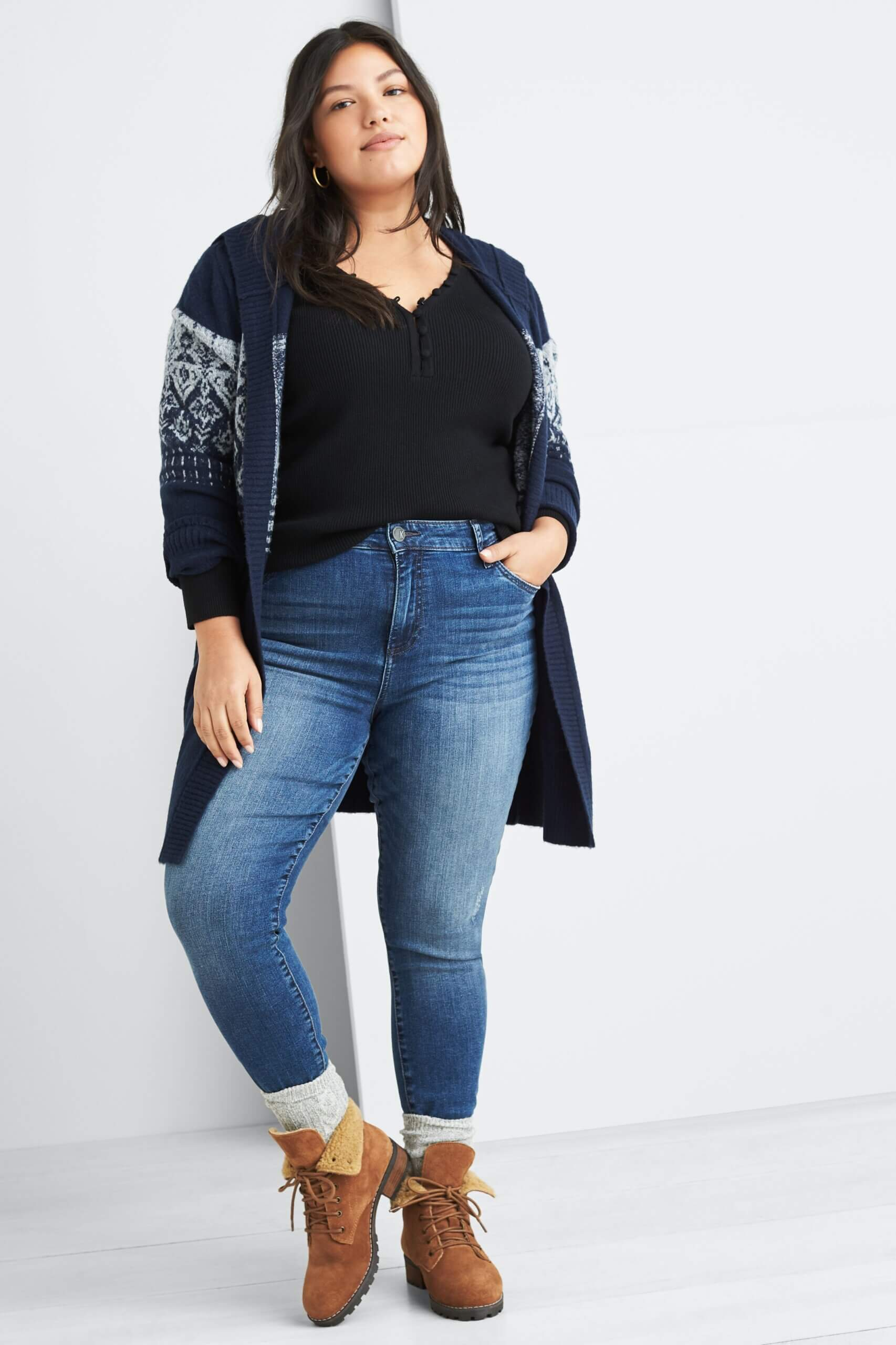 Stitch Fix Women's model wearing navy pullover, navy fair isle hooded cardigan, grey socks over her blue jeans and brown combat booties.