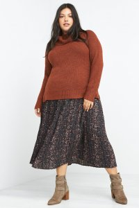 Stitch Fix model wearing plus-size clothing featuring orange cowl neck sweater, abstract printed midi skirt with taupe boots.
