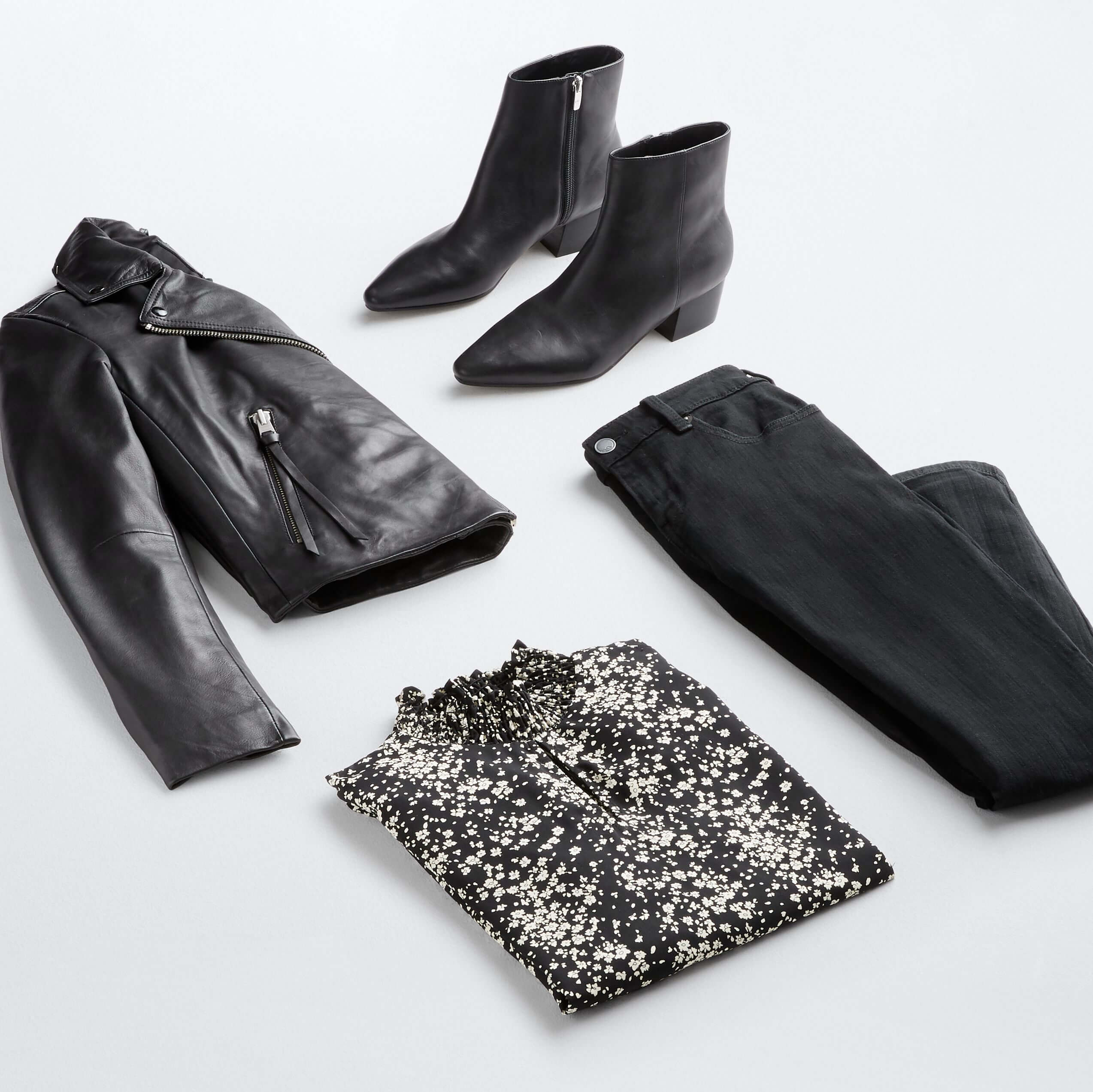 Stitch Fix Women's outfit laydown featuring a black leather jacket, black booties, black jeans and a black mock-neck printed top.