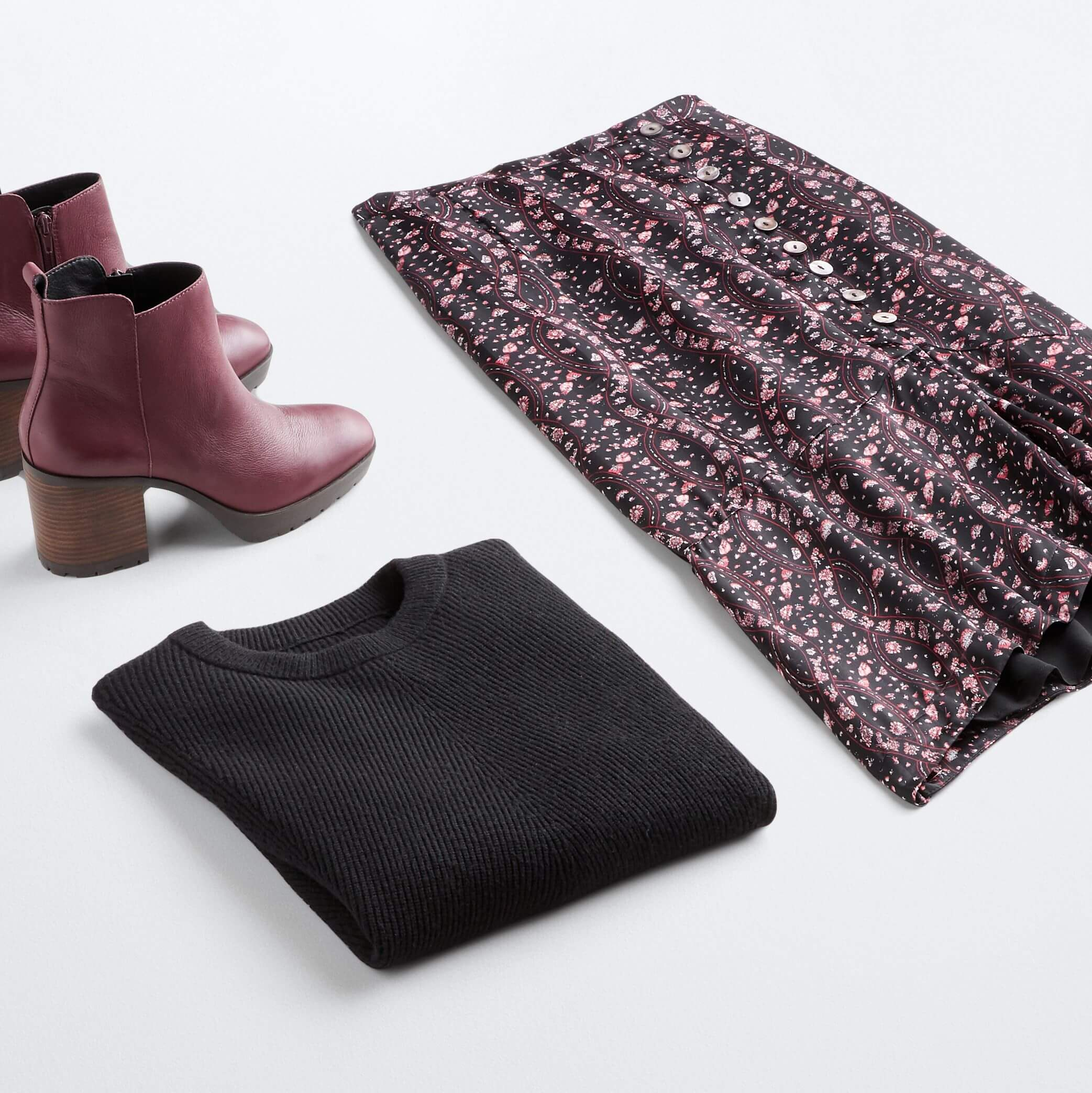 Stitch Fix Women's outfit laydown featuring purple floral skirt, black pullover sweater and purple heeled booties.