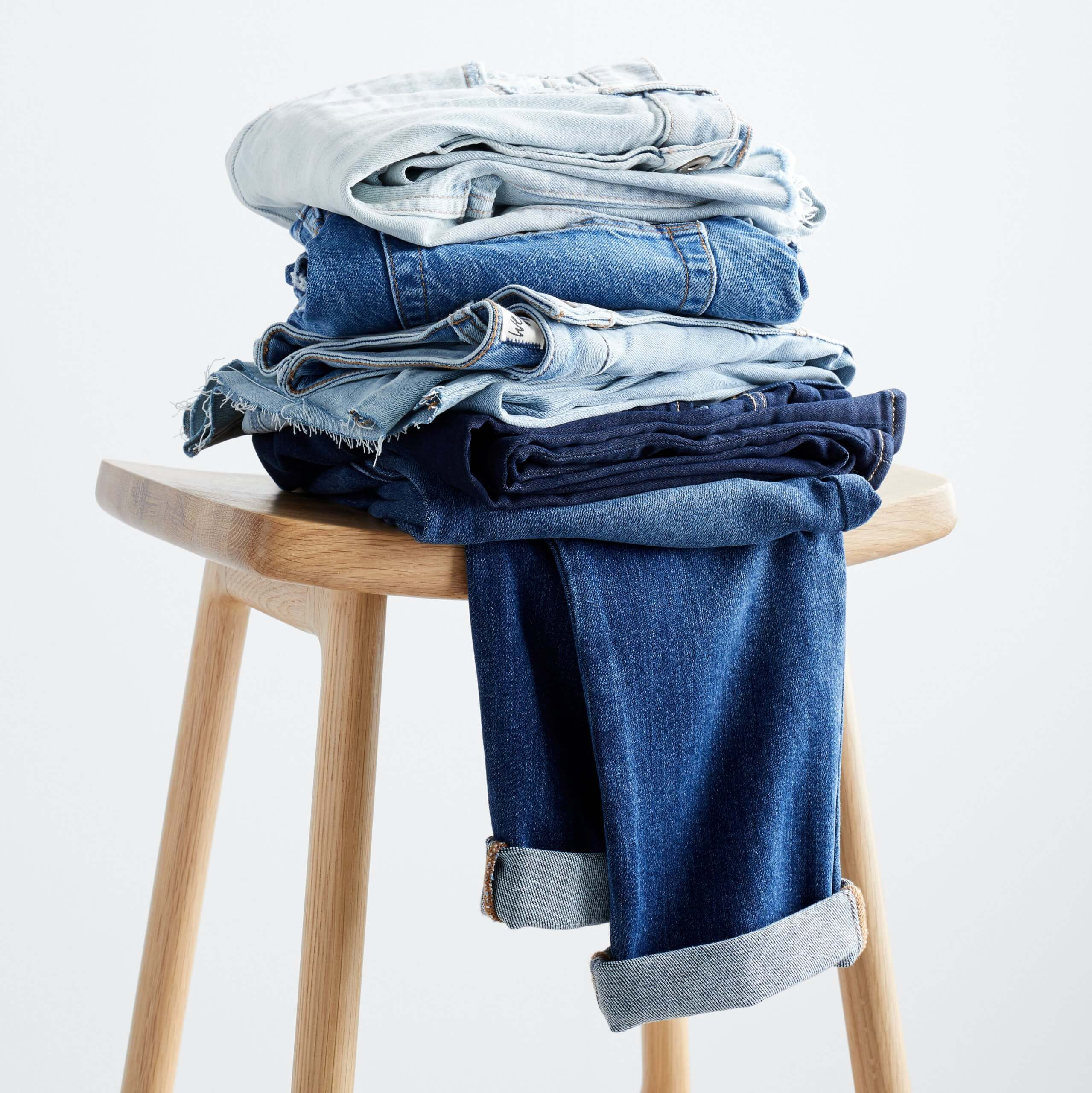 Stitch Fix women's folded jeans in different washes on wooden stool.