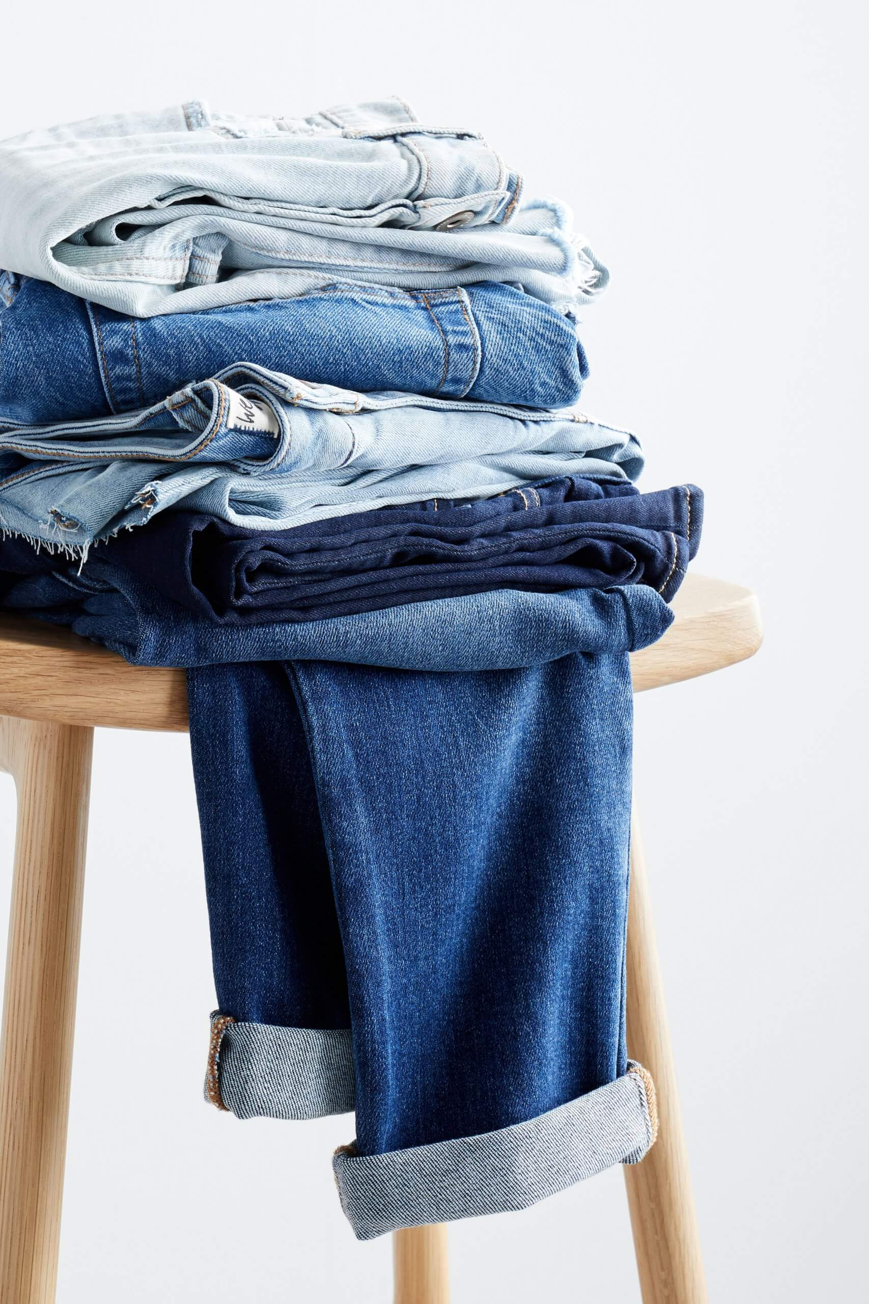 Stitch Fix women's blue jeans in various washes folded and stacked on a wooden stool.