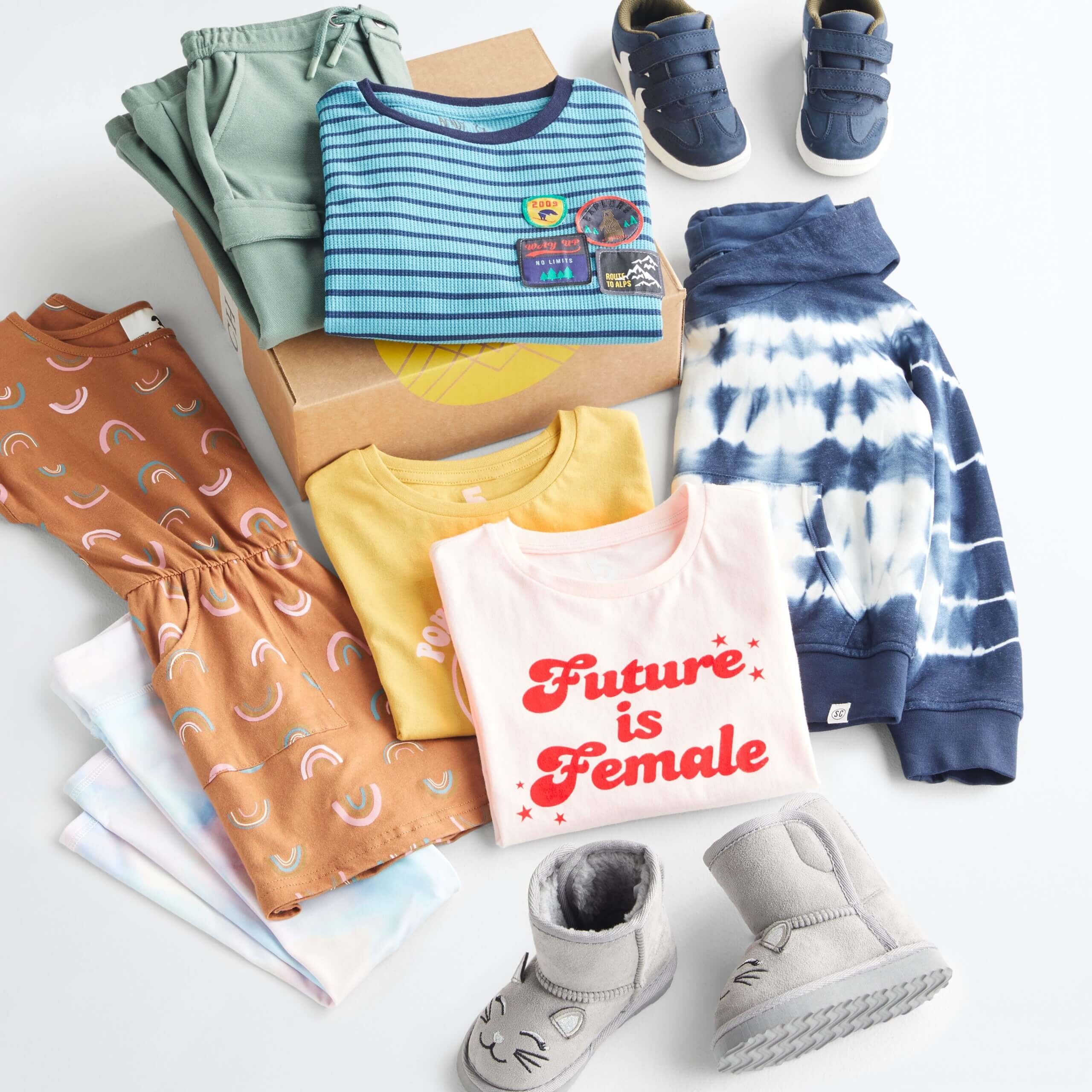 Stitch Fix Kid's outfit laydown featuring green pants and blue striped shirt on Stitch Fix delivery box, next to navy blue sneakers, navy blue tie-dye hoodie, pink and yellow t-shirts, silver boots, brown dress with rainbow print and light blue and light pink tie-dye leggings.