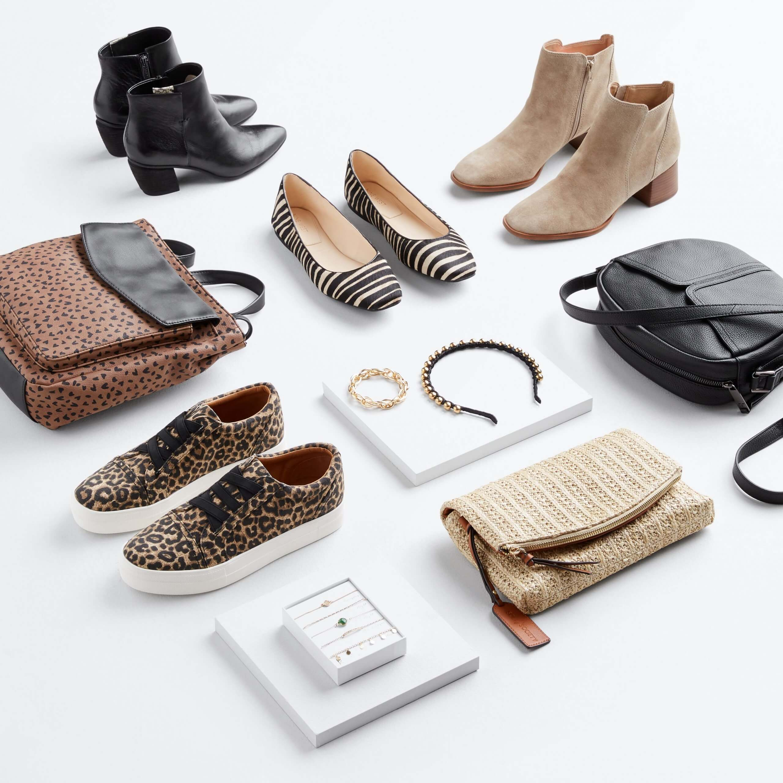 Stitch Fix Women's laydown featuring black heeled booties, black striped flats, tan heeled booties, black purse, tan clutch, animal print sneakers and animal print purse on the floor with black headband and gold bracelets on white blocks.