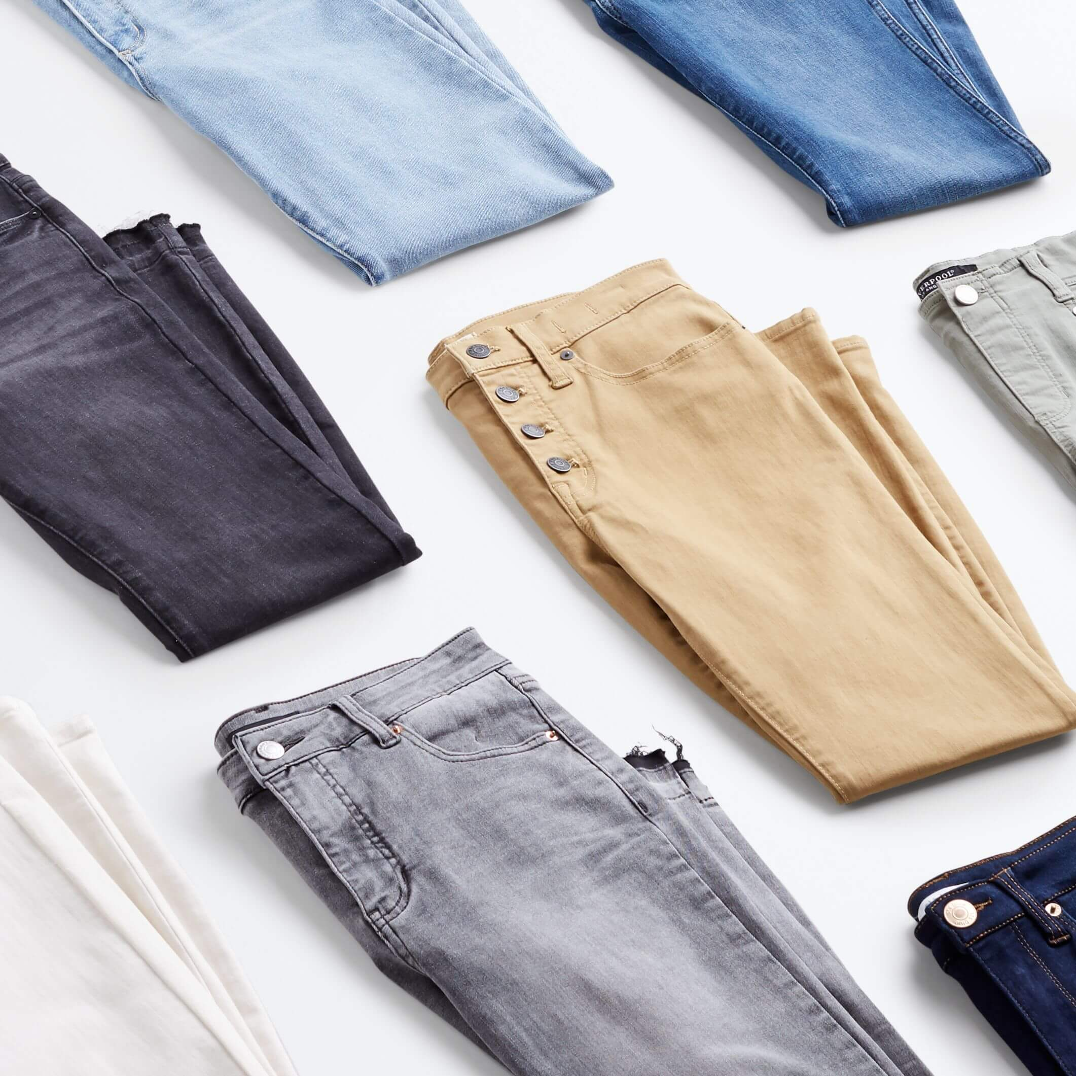 Stitch Fix Women's jeans in blue, gray, white and khaki folded in half.