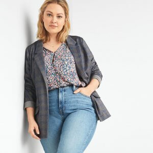 Stitch Fix model wearing women's floral blouse with plaid blazer and light wash denim leaning against a wall.