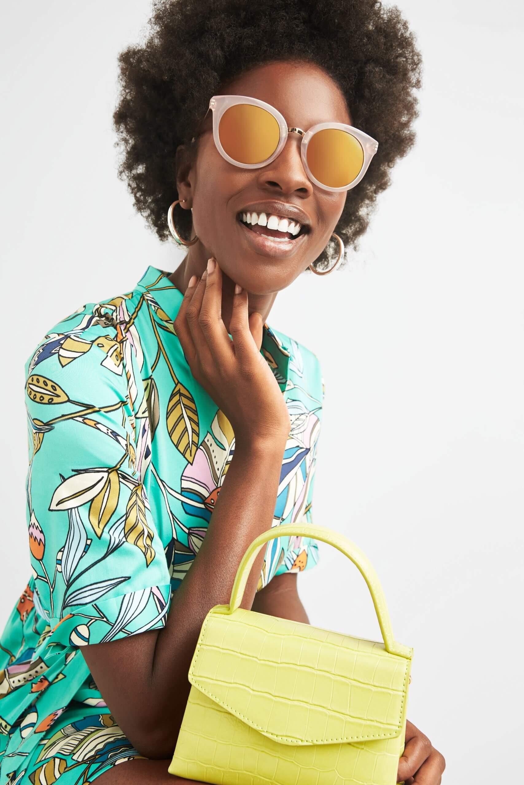 Stitch Fix Women's model wearing gold hoop earrings, sunglasses, green leaf-print romper and a lime green clutch.