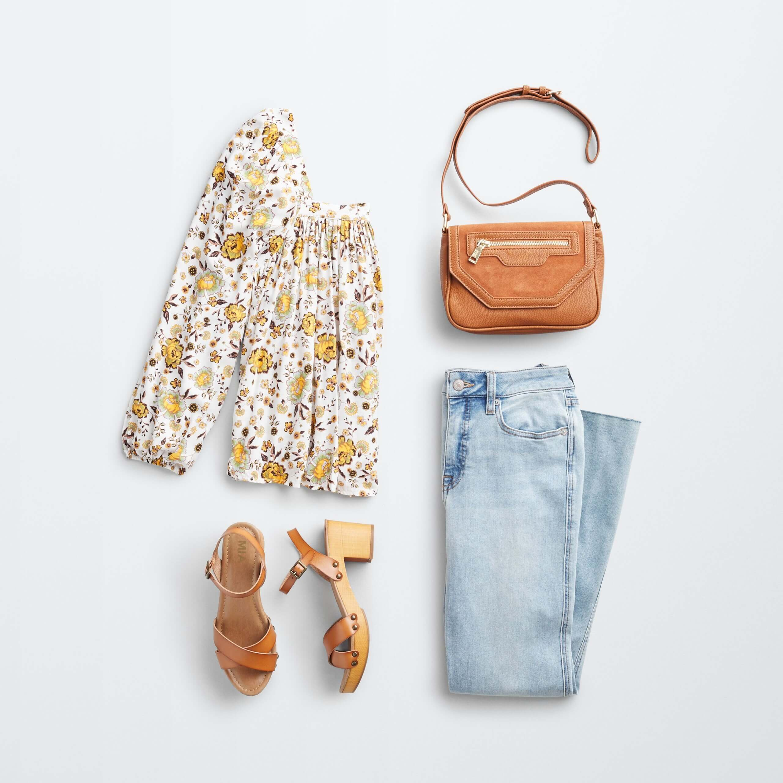 Stitch Fix Women's outfit laydown featuring white boho blouse with yellow florals, brown wooden heels, light wash cropped flare jeans and brown crossbody bag.