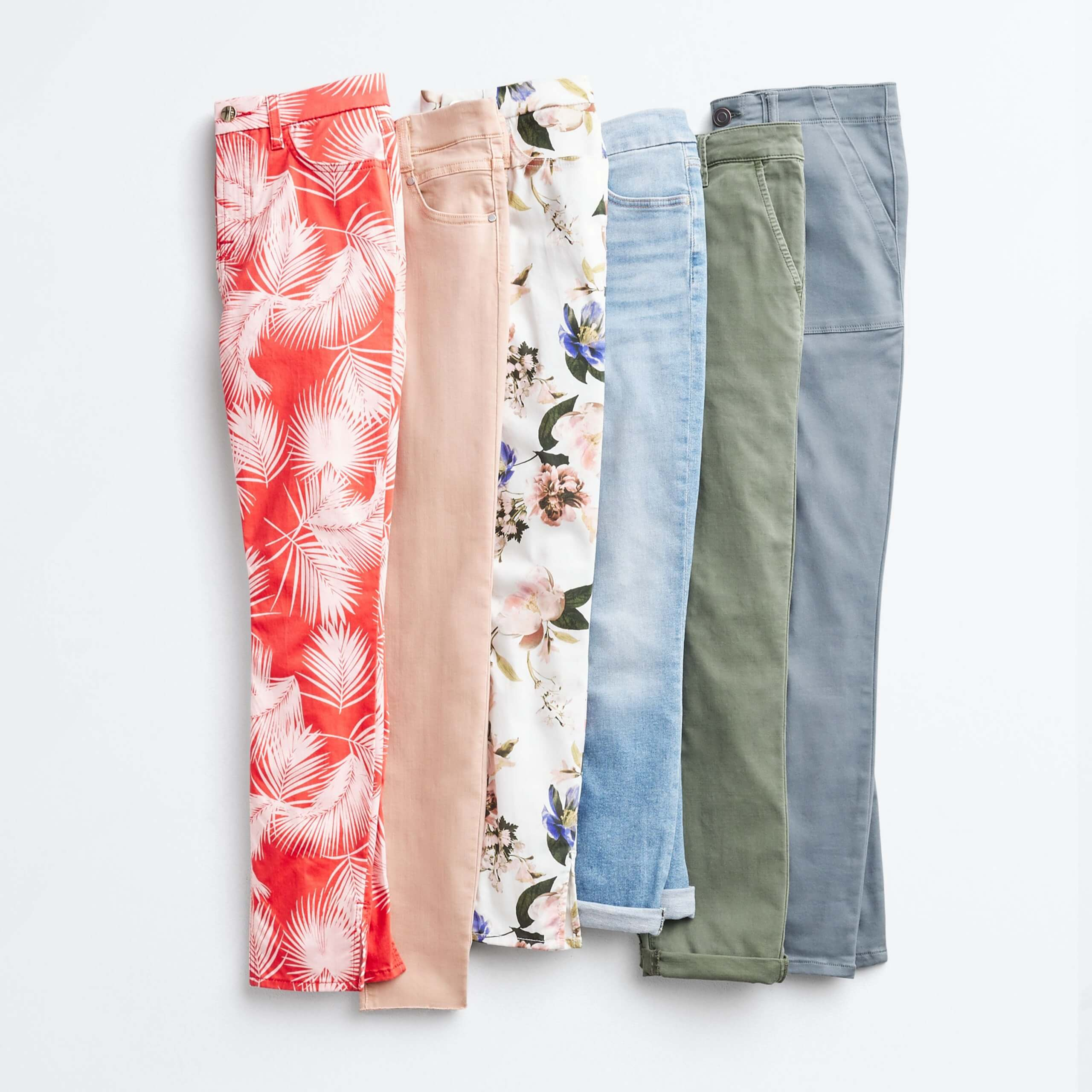 Stitch Fix Women's outfit laydown of skinny jeans in orange tropical print, blush pink, white floral, light blue, olive green and light blue.