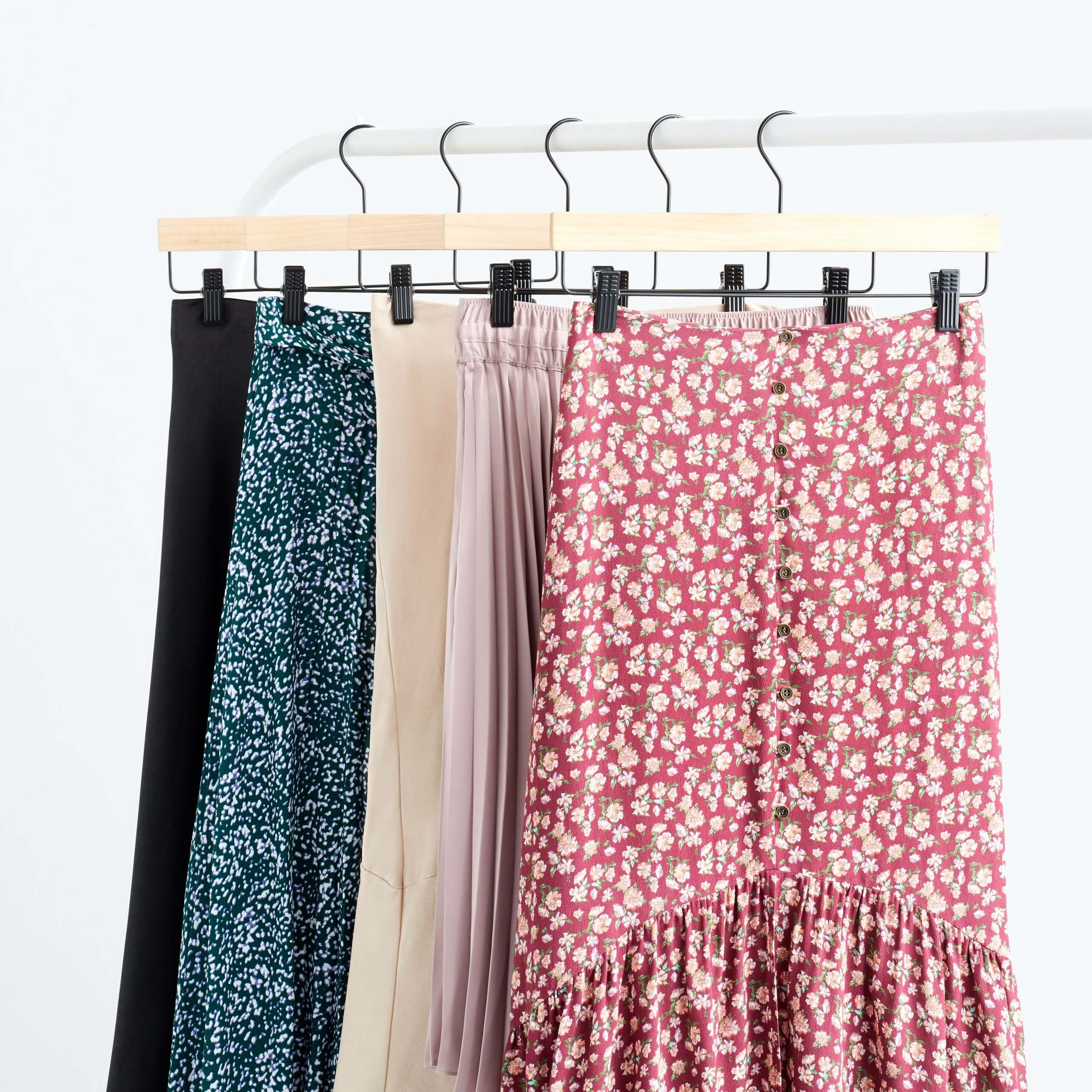 Stitch Fix Women's rack image of skirts in red floral, blush pink, beige, teal floral and black on wooden hangers.