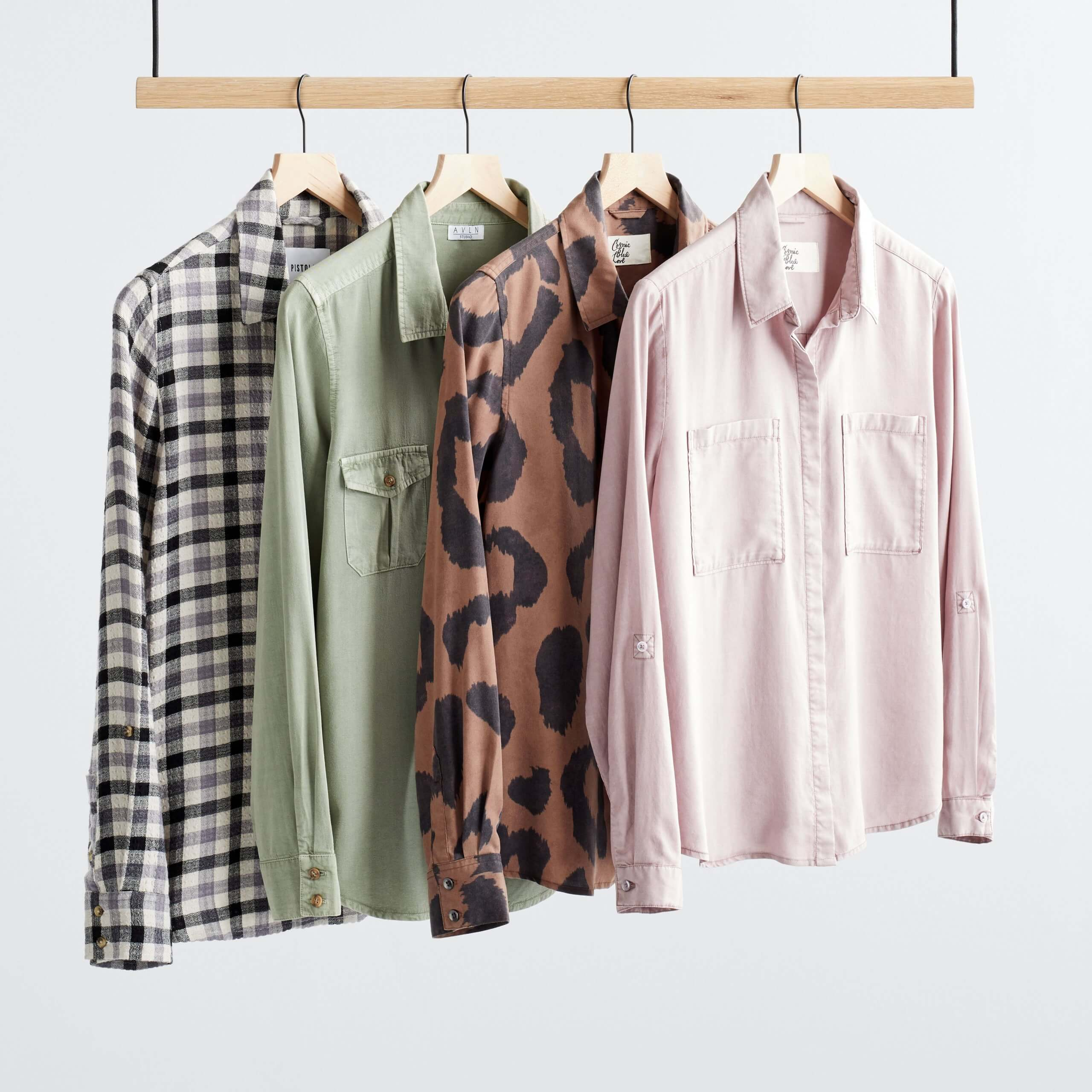 Stitch Fix Women's rack featuring button-front shirts on wooden hangers in black and white plaid, olive green, brown leopard print and light pink.