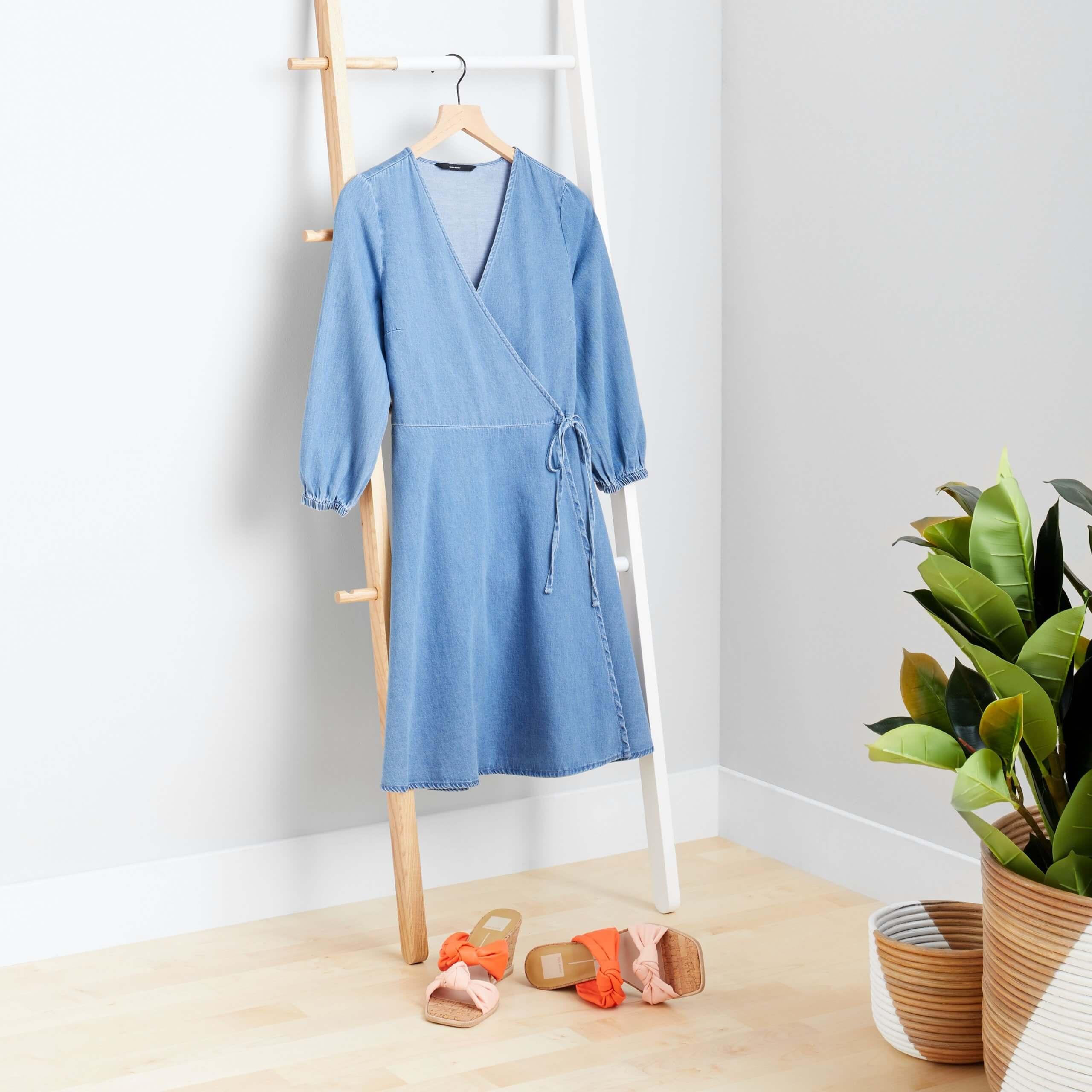 Stitch Fix Women's blue wrap dress hanging on wooden ladder next to orange and pink slide wedges.