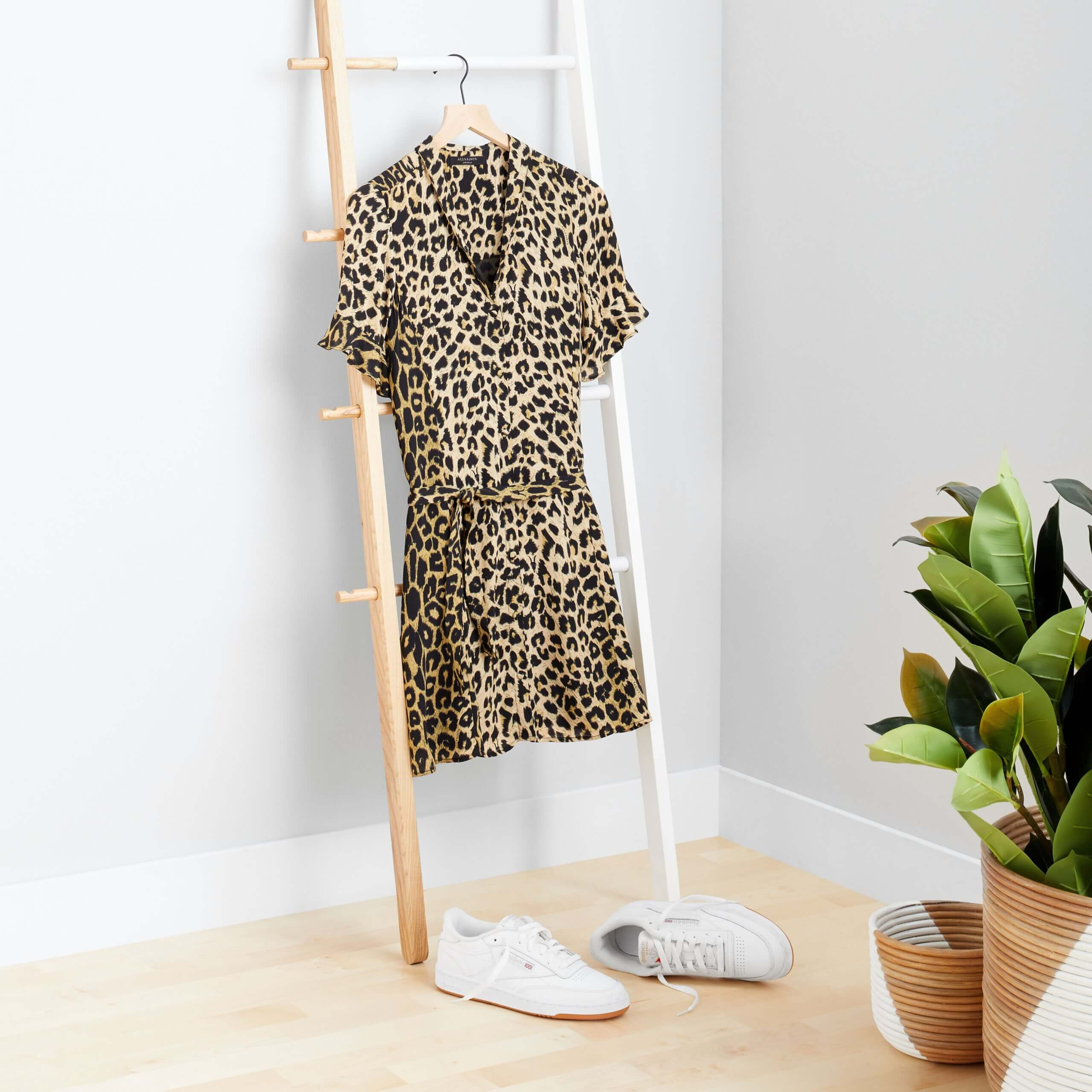 Stitch Fix Women's rack image with brown cheetah print dress hanging on wooden rack with white sneakers on the floor.