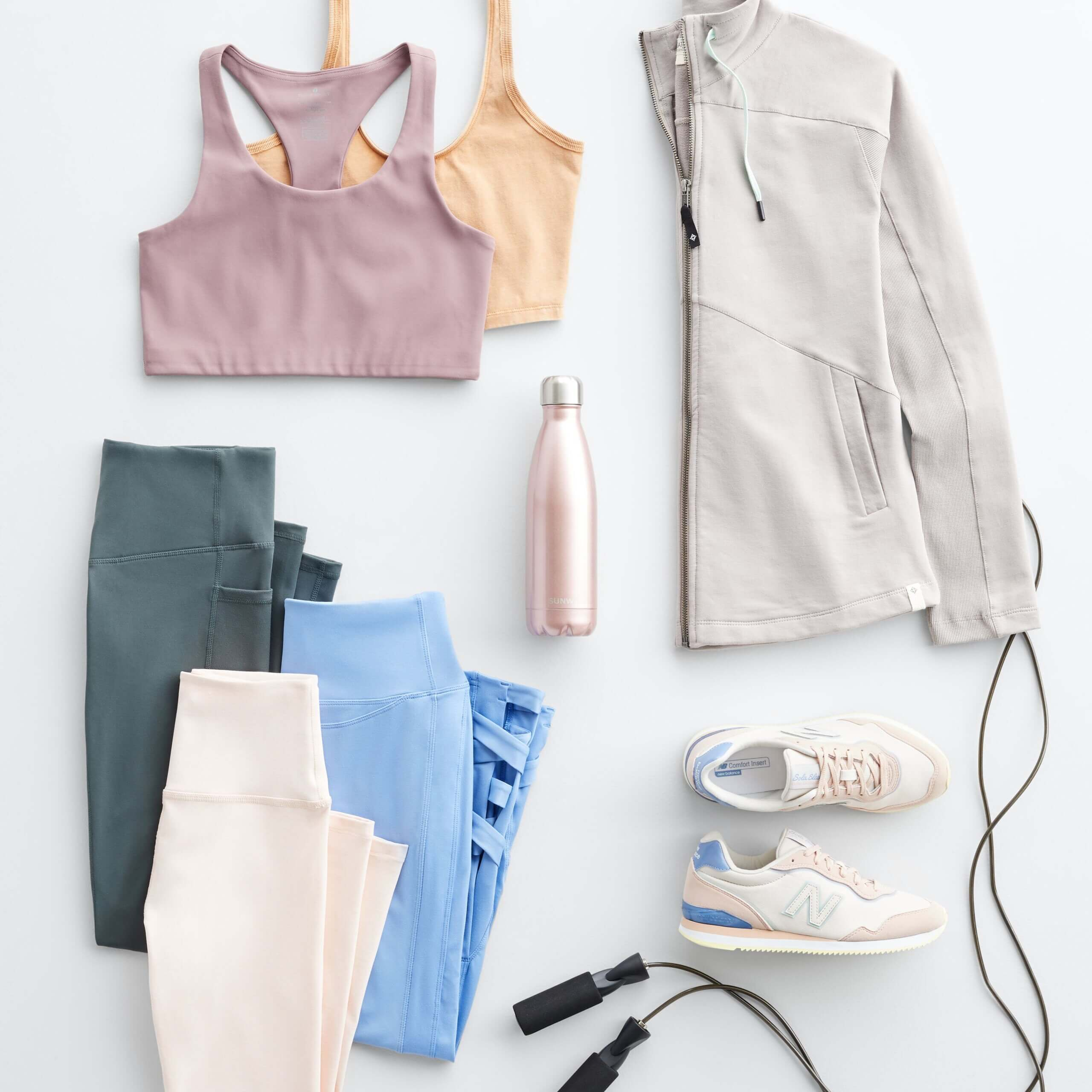 Stitch Fix Women's laydown featuring sports bras in mauve and orange, leggings in grey, light blue and blush, grey active jacket and white sneakers with pink and blue accents.