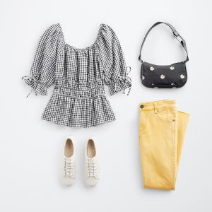 Stitch Fix women's outfit laydown featuring a puff sleeve black and white striped top, patterned black purse, yellow jeans and white sneakers.