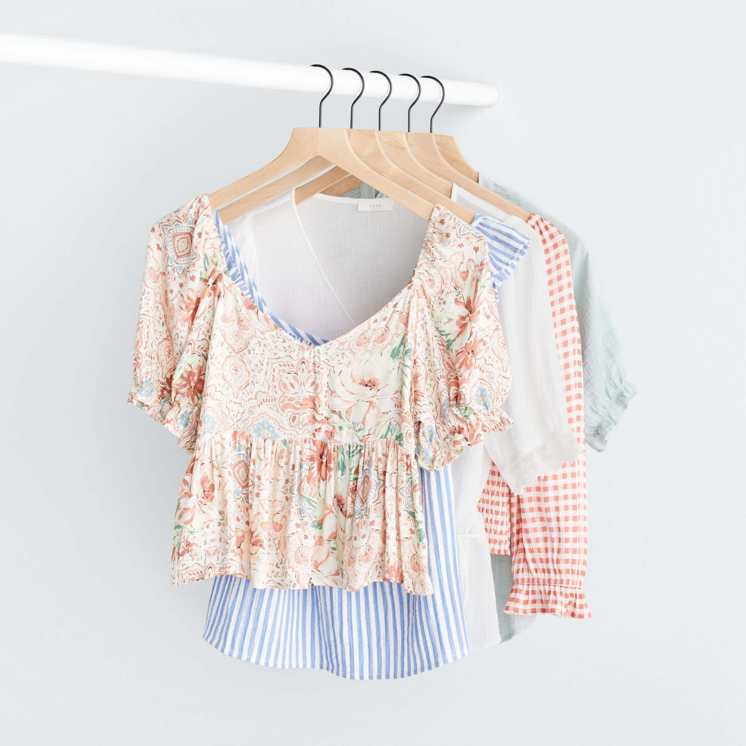 Stitch Fix Women's rack image with white peplum top with pink florals, blue and white striped ruffle tank, white peplum top, pink and white gingham top and green ruffle sleeve top hanging on white pole.