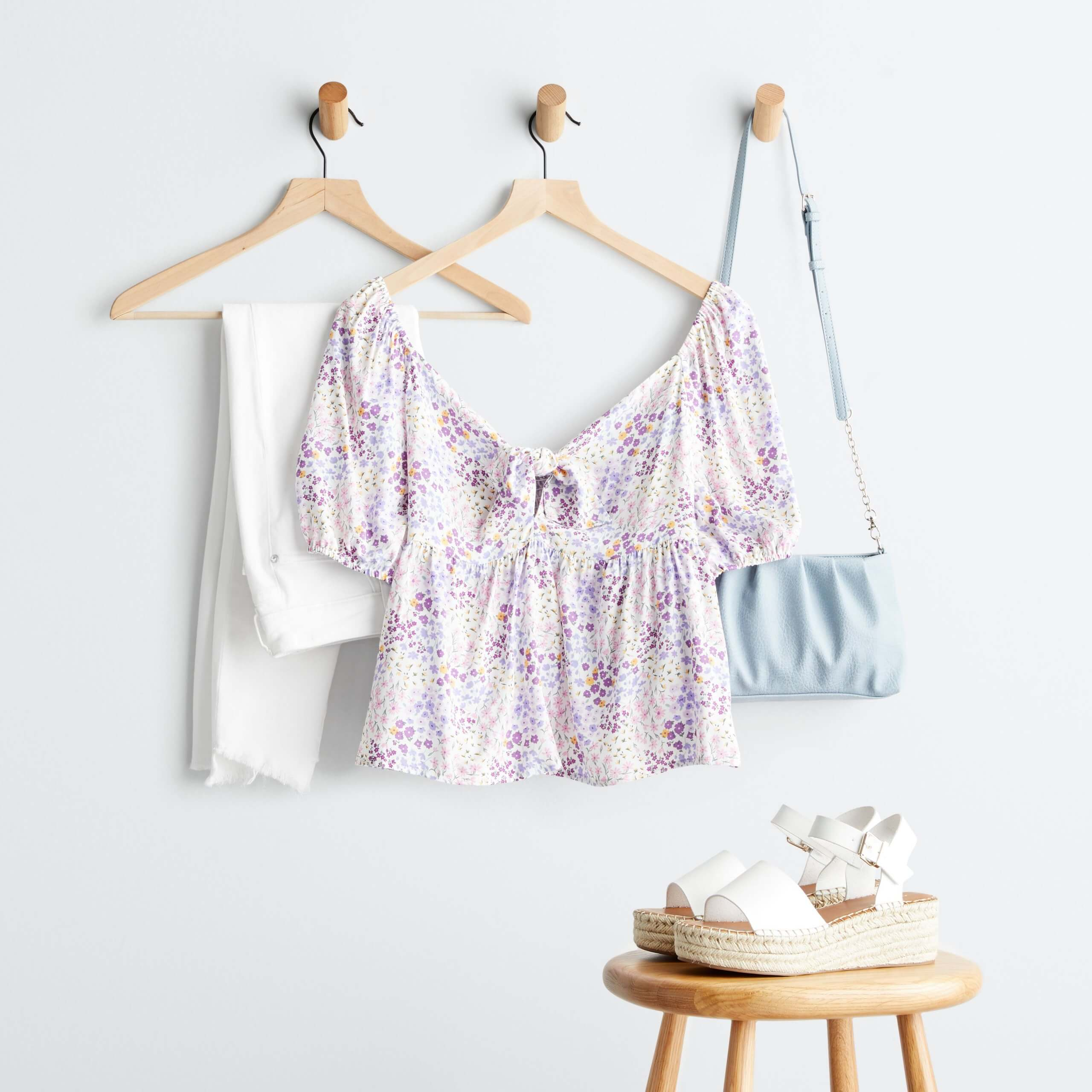 Stitch Fix Women's purple printed blouse with puff sleeves on hanger, white denim on hanger, blue purse on hanger and espadrille wedges on stool.