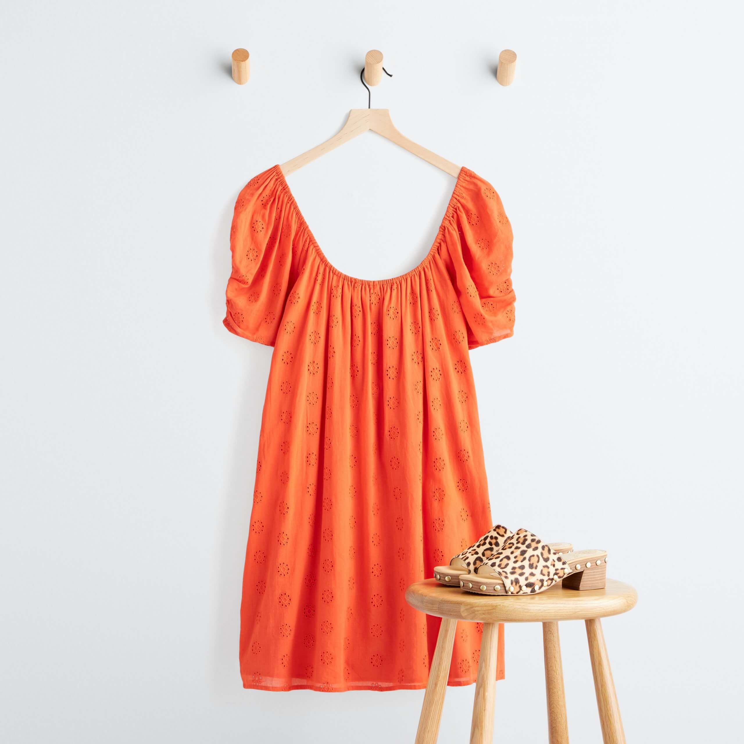 Stitch Fix Women's orange textured dress hanging on a wooden hanger and leopard-print heeled mules on a wooden stool.
