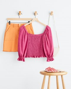 Stitch Fix women's orange mini skirt, pink puff sleeve top and a white purse hanging behind a stool with pink sandals on top.