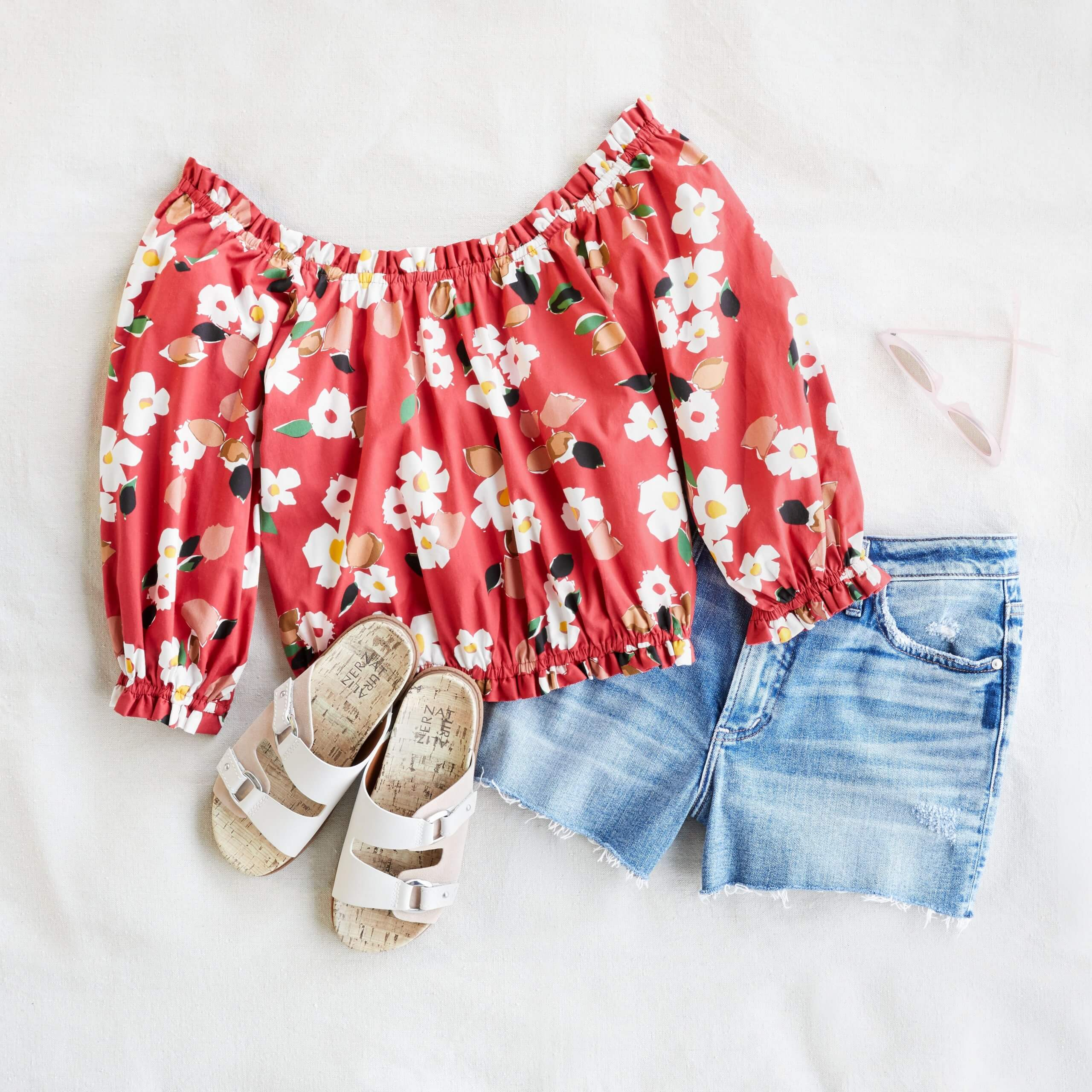 Stitch Fix women's 4th of July outfit laydown featuring blue denim shorts, white sandals, and red and white floral print blouse.