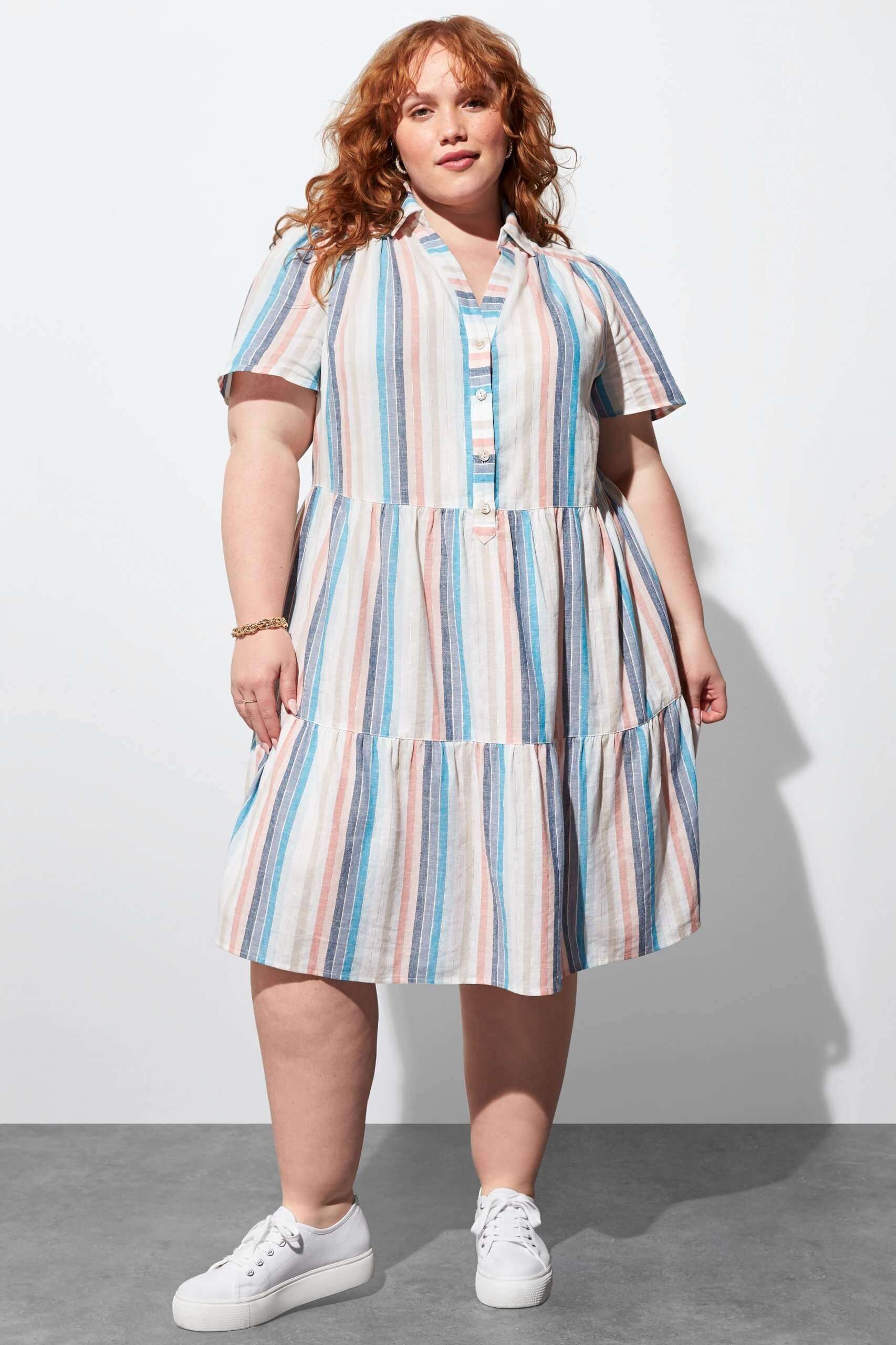 Stitch Fix Women's model wearing white, pink and blue striped shirt dress and white sneakers.