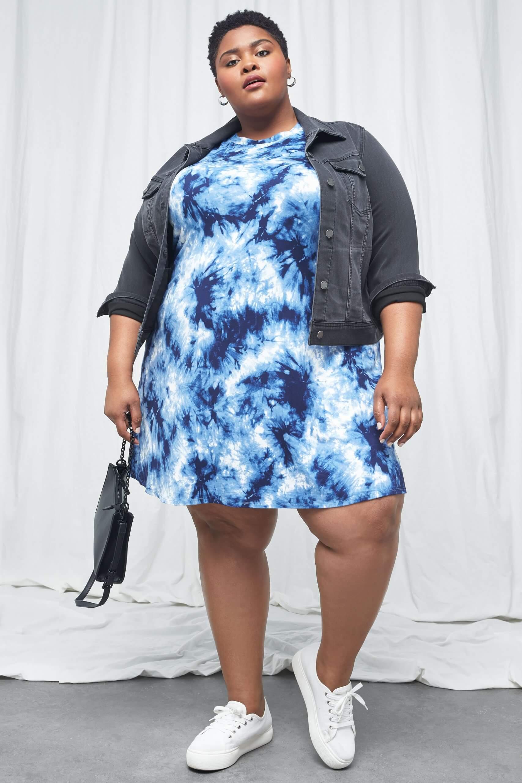 Stitch Fix Women's model wearing blue tie-dye knit dress with grey denim jacket and white sneakers, holding a black purse.