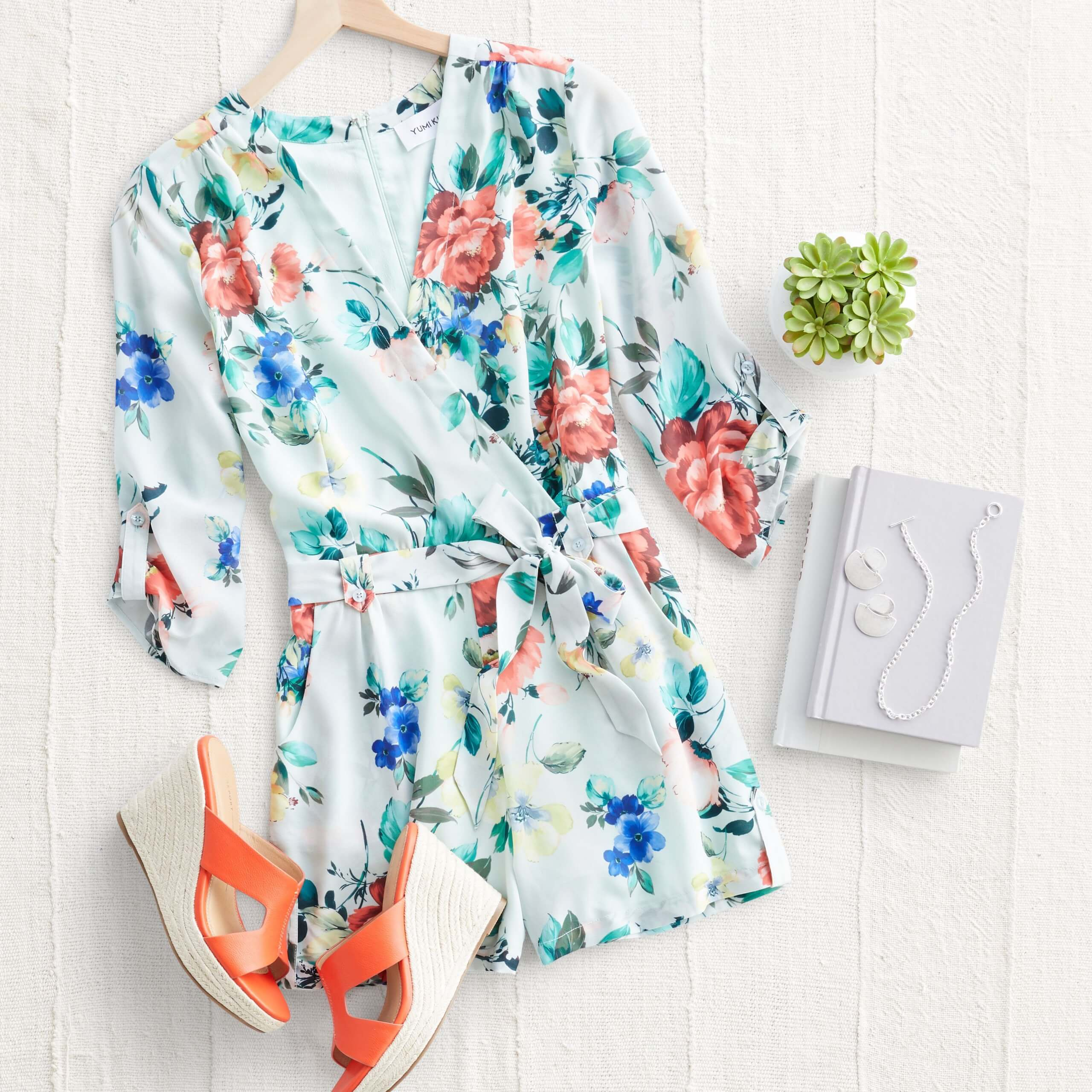 Stitch Fix Women's outfit laydown featuring white floral romper, coral wedges and silver drop earrings and necklace on white book.