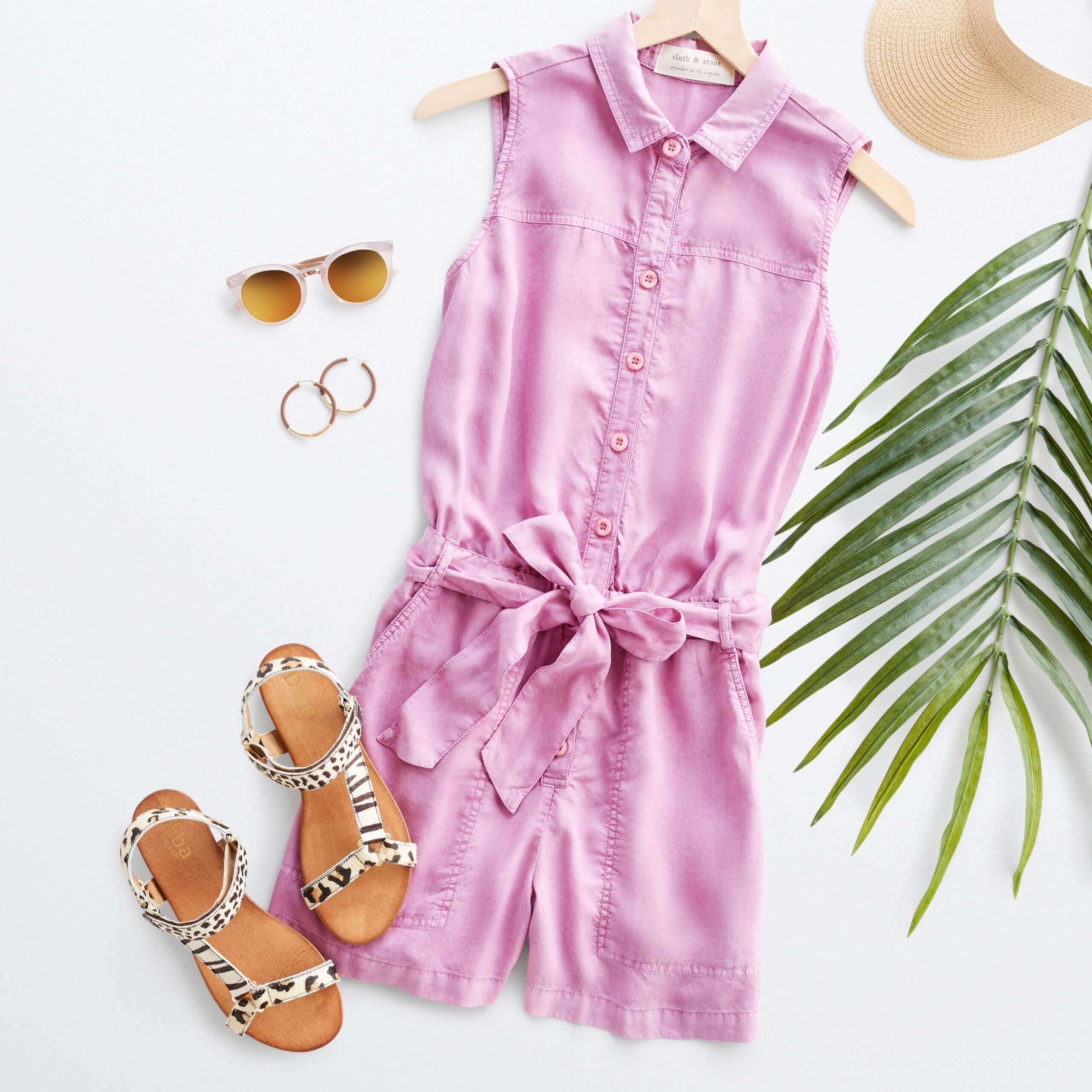 Stitch Fix women's outfit laydown featuring pink collared romper with button-front and tie-waist detail next to brown animal-print sandals and gold hoop earrings.