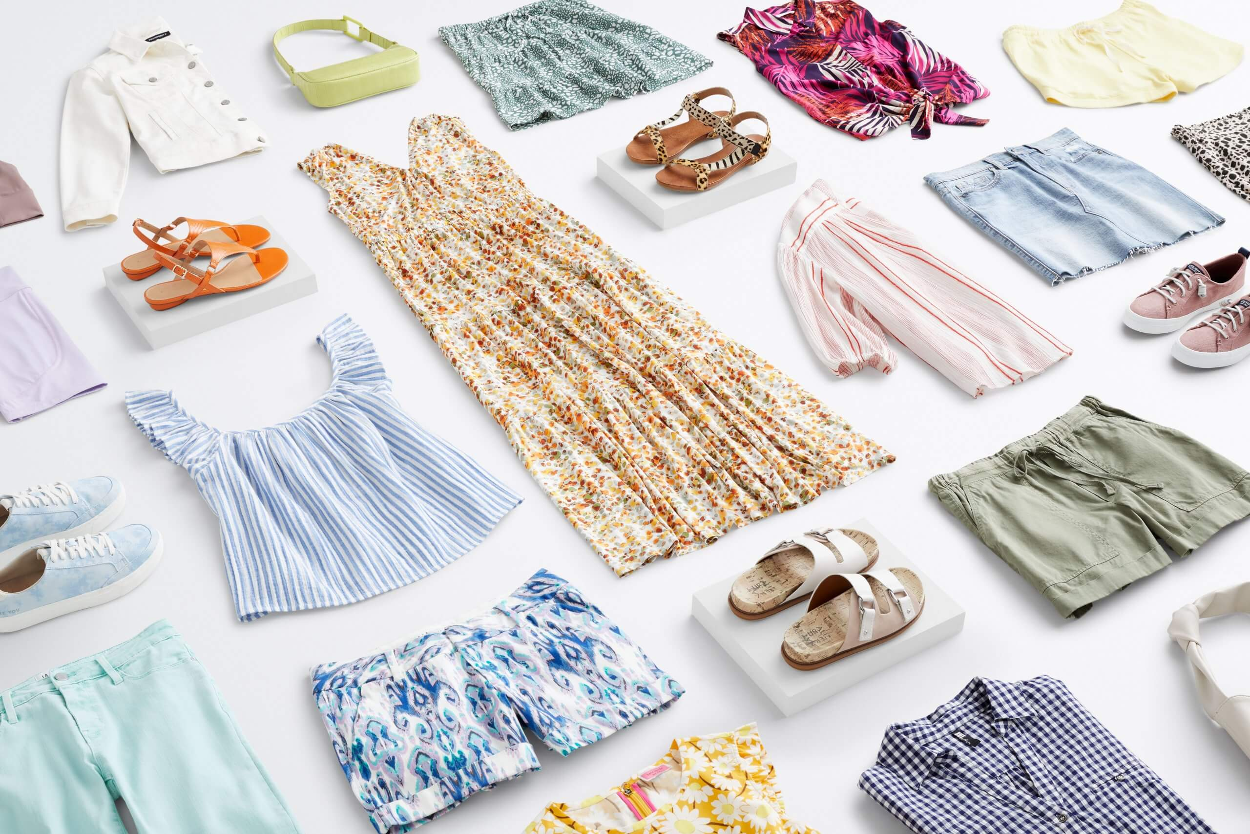 Stitch Fix Women's outfit laydown featuring a wide range of summer pieces including white denim jacket, shorts and skirts in blue, green and yellow tones, printed tank tops, floral maxi dress, sandals and sneakers in various tones.