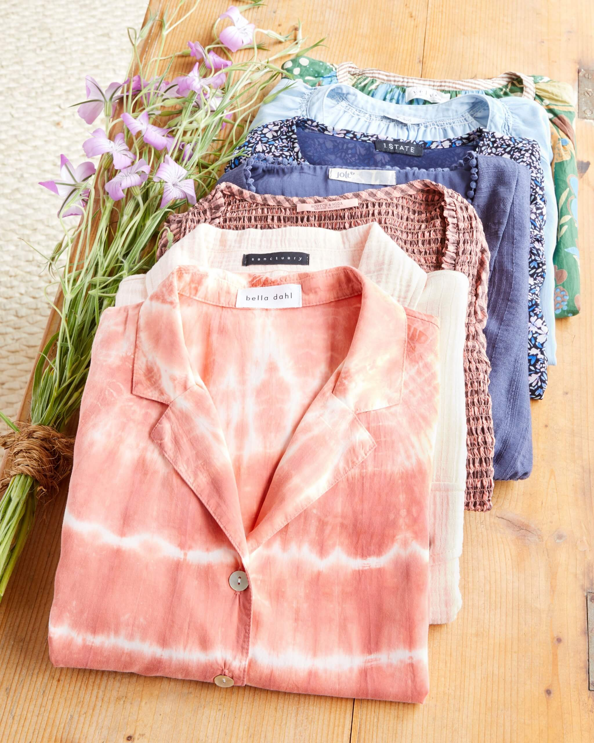 Stitch Fix Women's outfit laydown featuring folded shirts in a pile in pink, white, purple, blue and green tones on a wooden table.