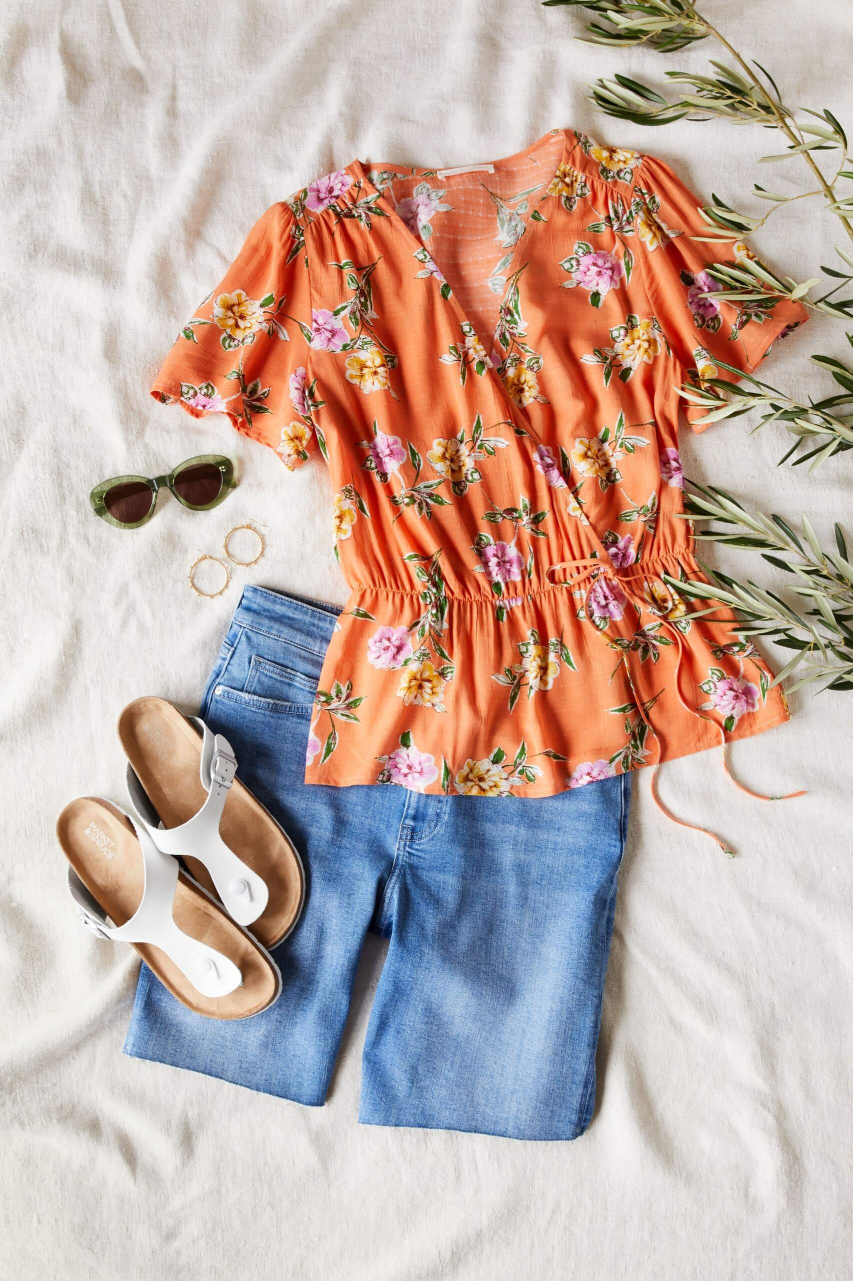 Stitch Fix Women's outfit laydown featuring orange floral wrap shirt, blue bermuda denim shorts, gold hoop earrings, white sandals and sunglasses.