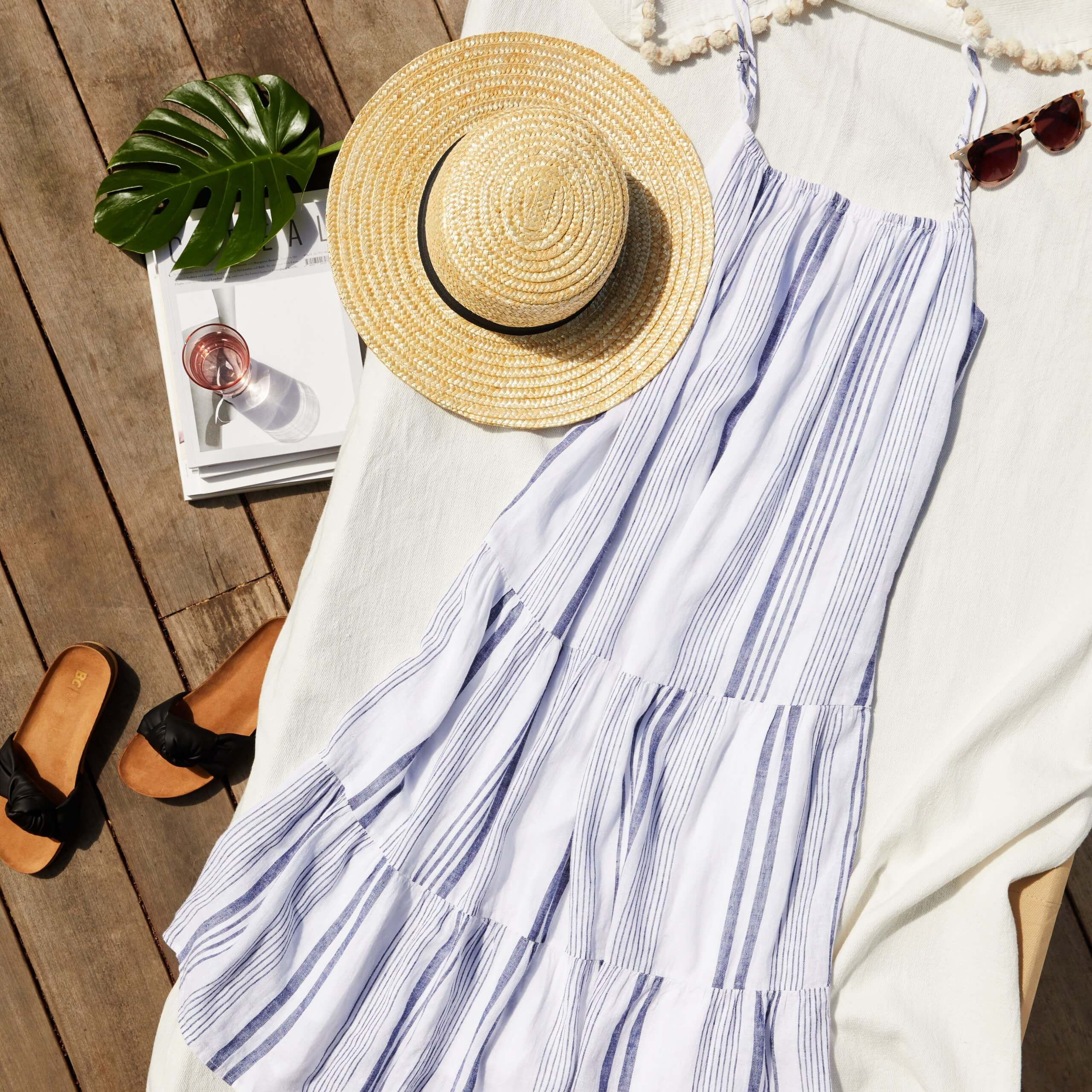 Stitch Fix women's boho outfit featuring blue stripe tiered maxi-dress with straw hat, sunglasses and slide sandals.