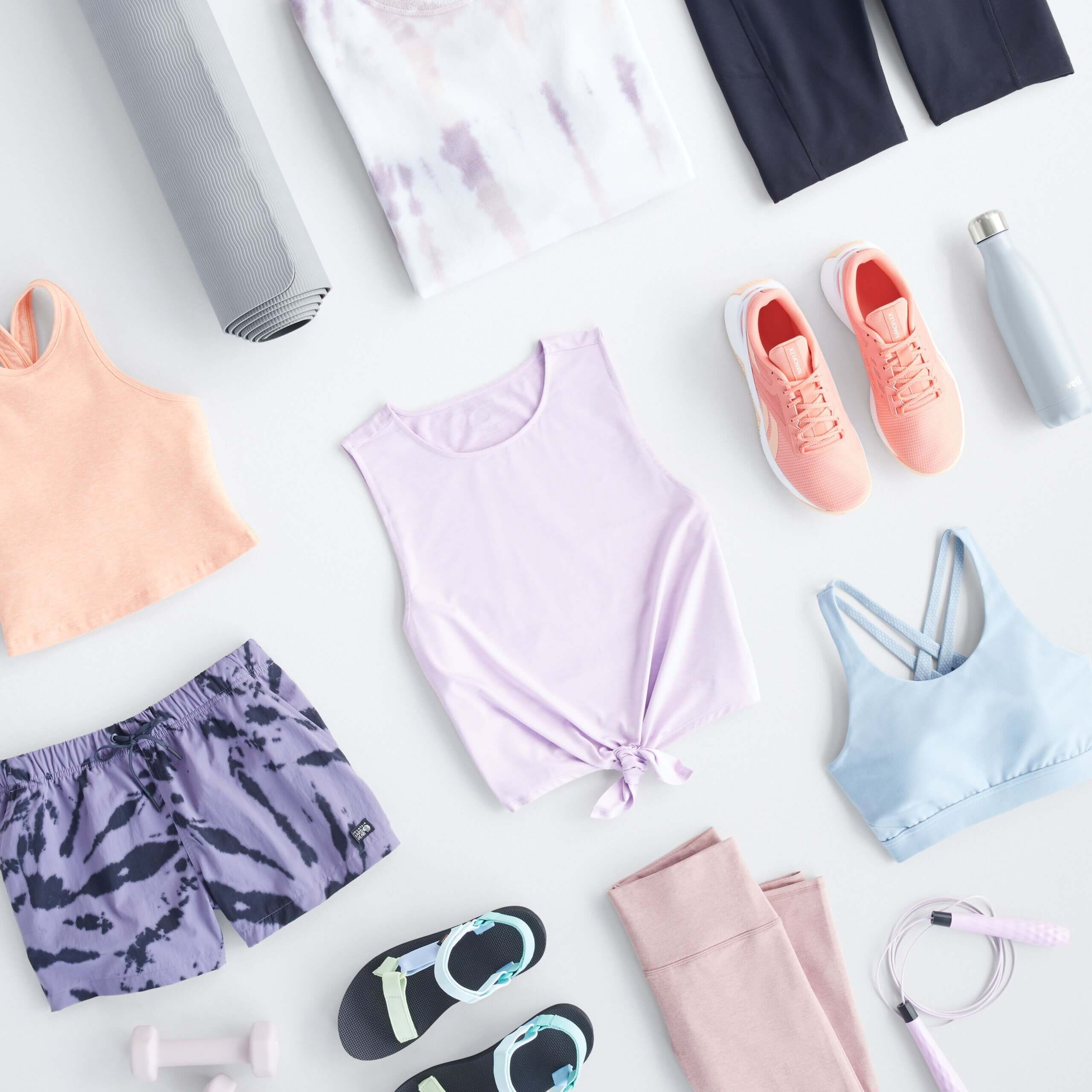 Stitch Fix Women's laydown featuring athletic tops in peach, lilac and baby blue, purple athletic shorts, navy bike shorts, pink sneaker and sandals.