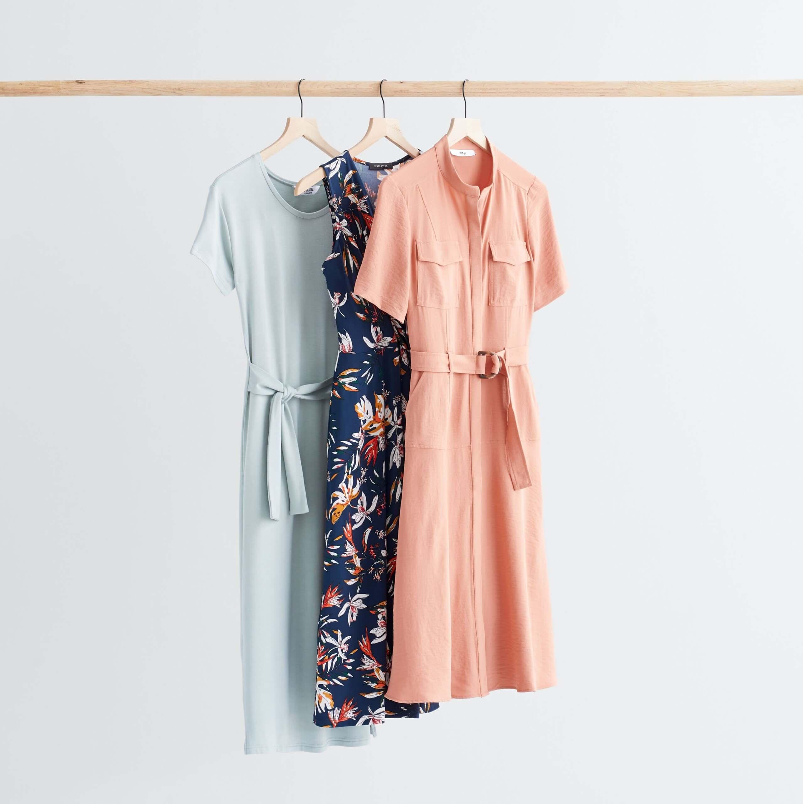 Stitch Fix Women's rack image featuring pink shirt dress, navy floral dress and baby blue tie-waist dress hanging on wooden rack.