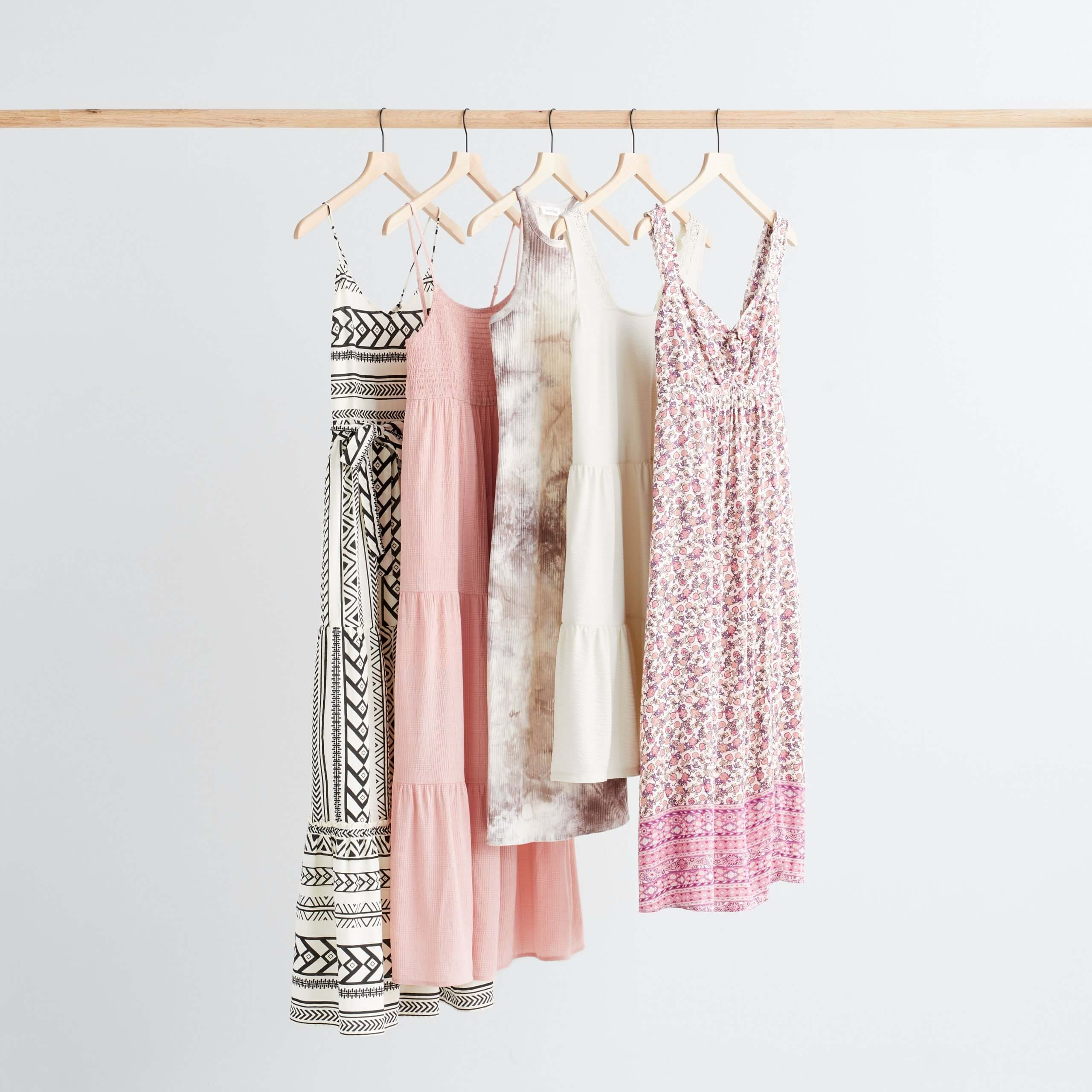 Stitch Fix Women's boho style dresses hanging in a variety of colors, prints and lengths.
