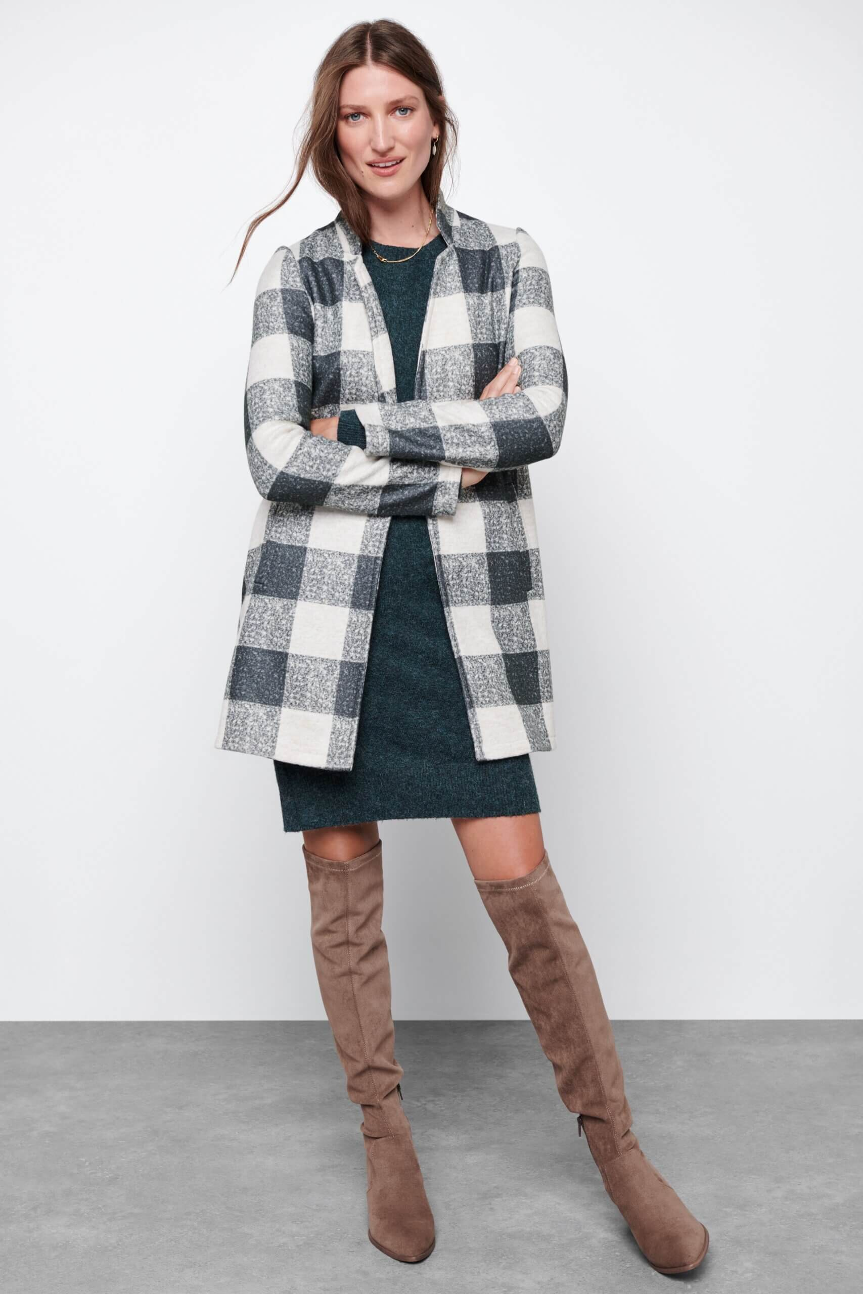Stitch Fix women's model wearing green dress, black and white checkered cardigan and taupe over-the-knee boots.